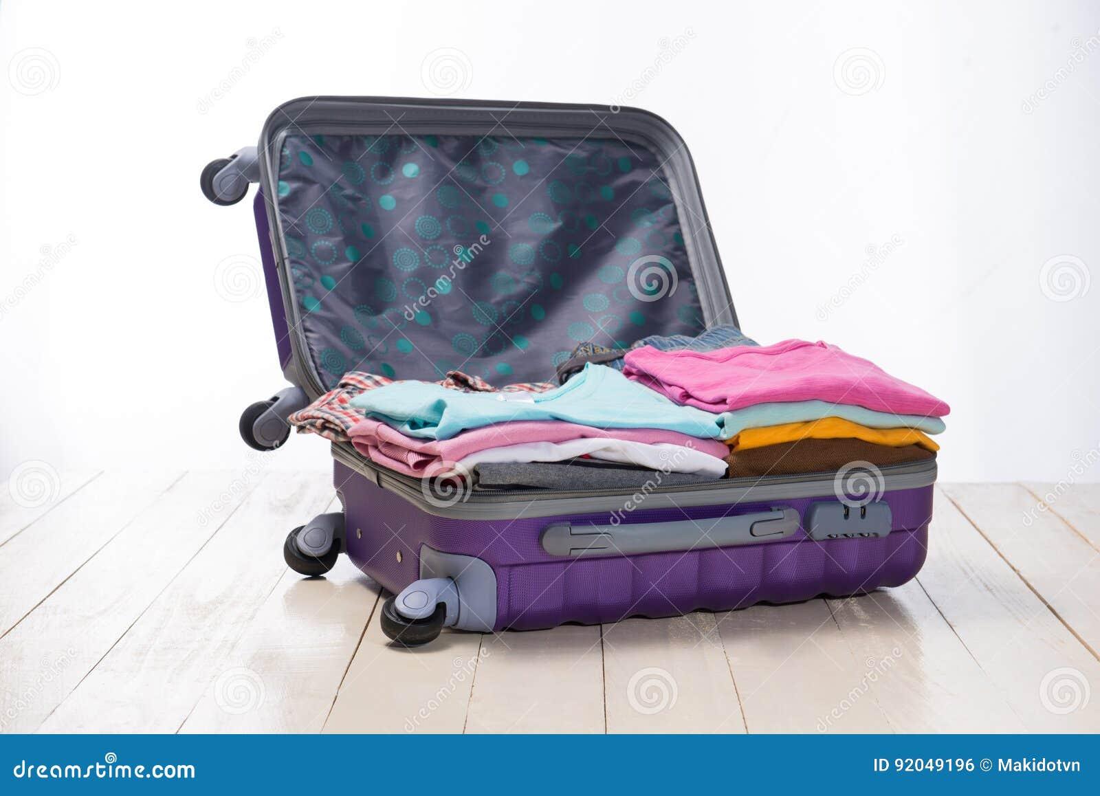 旅行和假期概念 打开旅客与衣物的` s袋子,