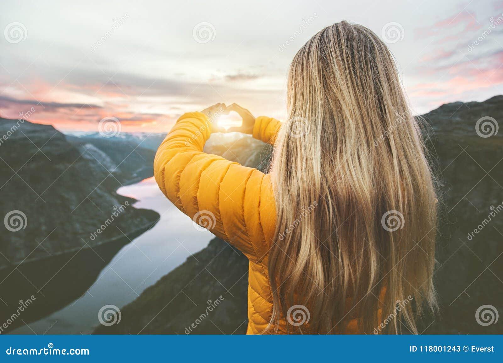 旅行在日落山的妇女递被塑造的心脏标志