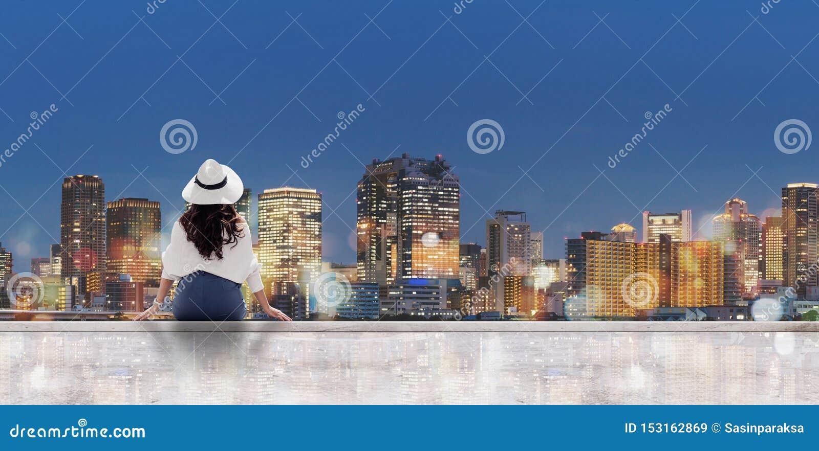 旅行在晚上在城市 白色帽子的年轻女人坐看大阪市的露台在晚上