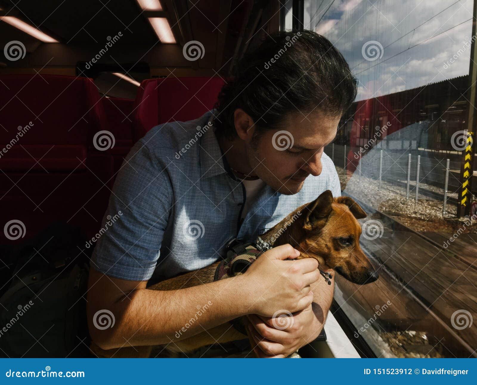 旅行在火车的人和他小的混杂的品种狗