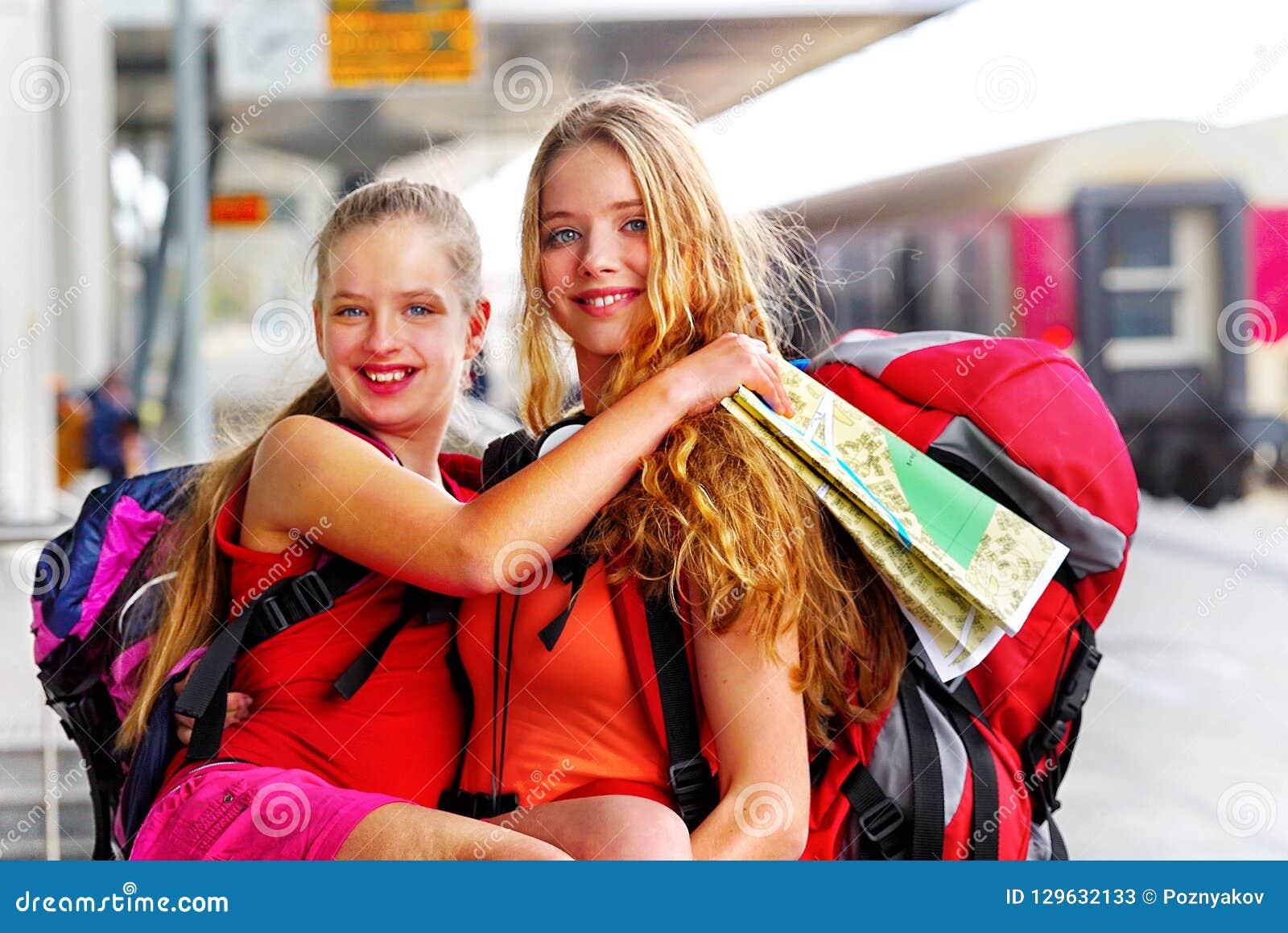 旅行家女孩女性背包和旅游业成套装备在火车站