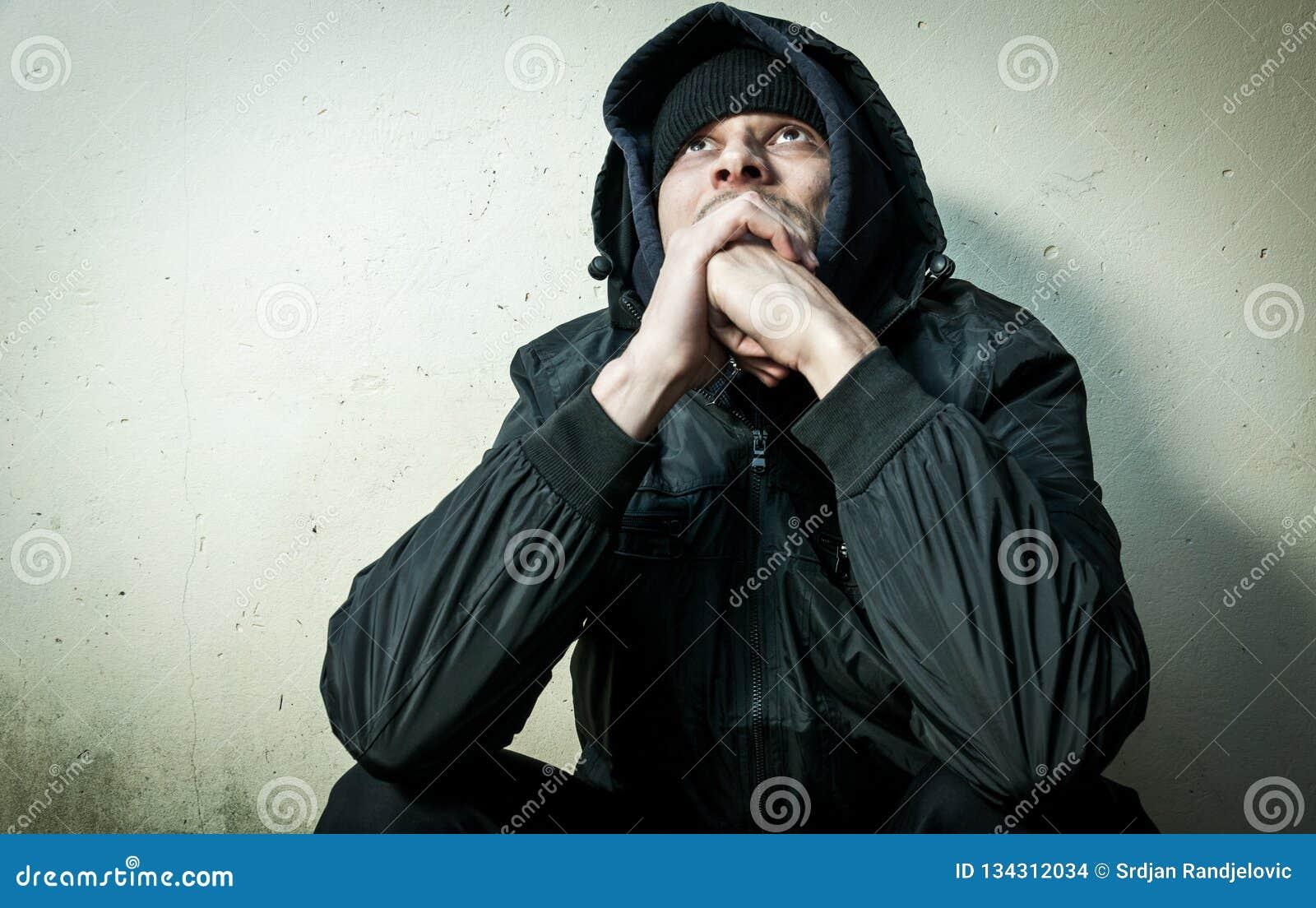 无家可归的人药物和酒精上瘾者单独坐和沮丧在感觉急切冷的冬季衣服的街道和孤独,