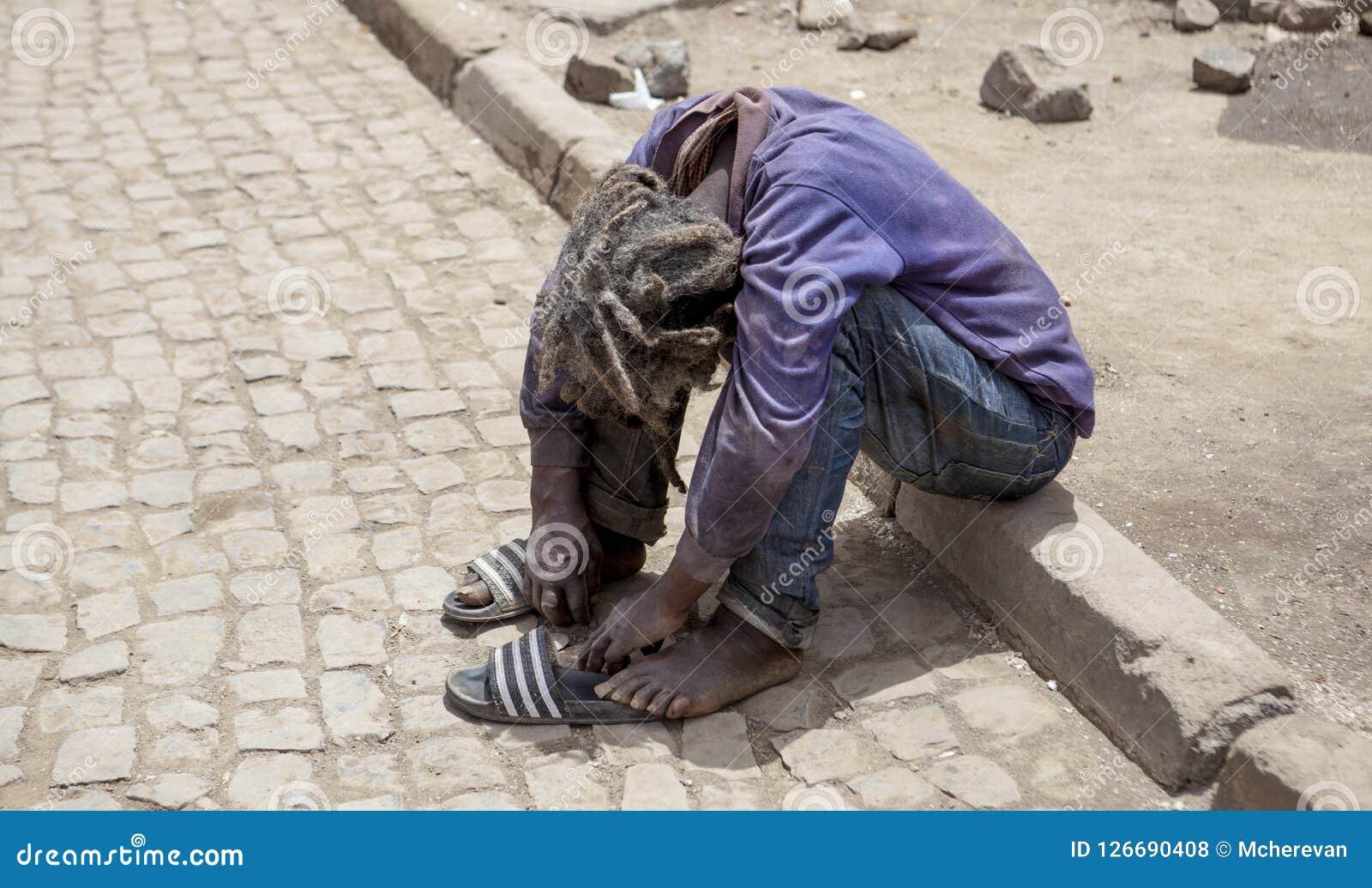 无家可归者,流浪汉 一个肮脏的有臭味的流浪者人是坐外部和哭泣充满哀情