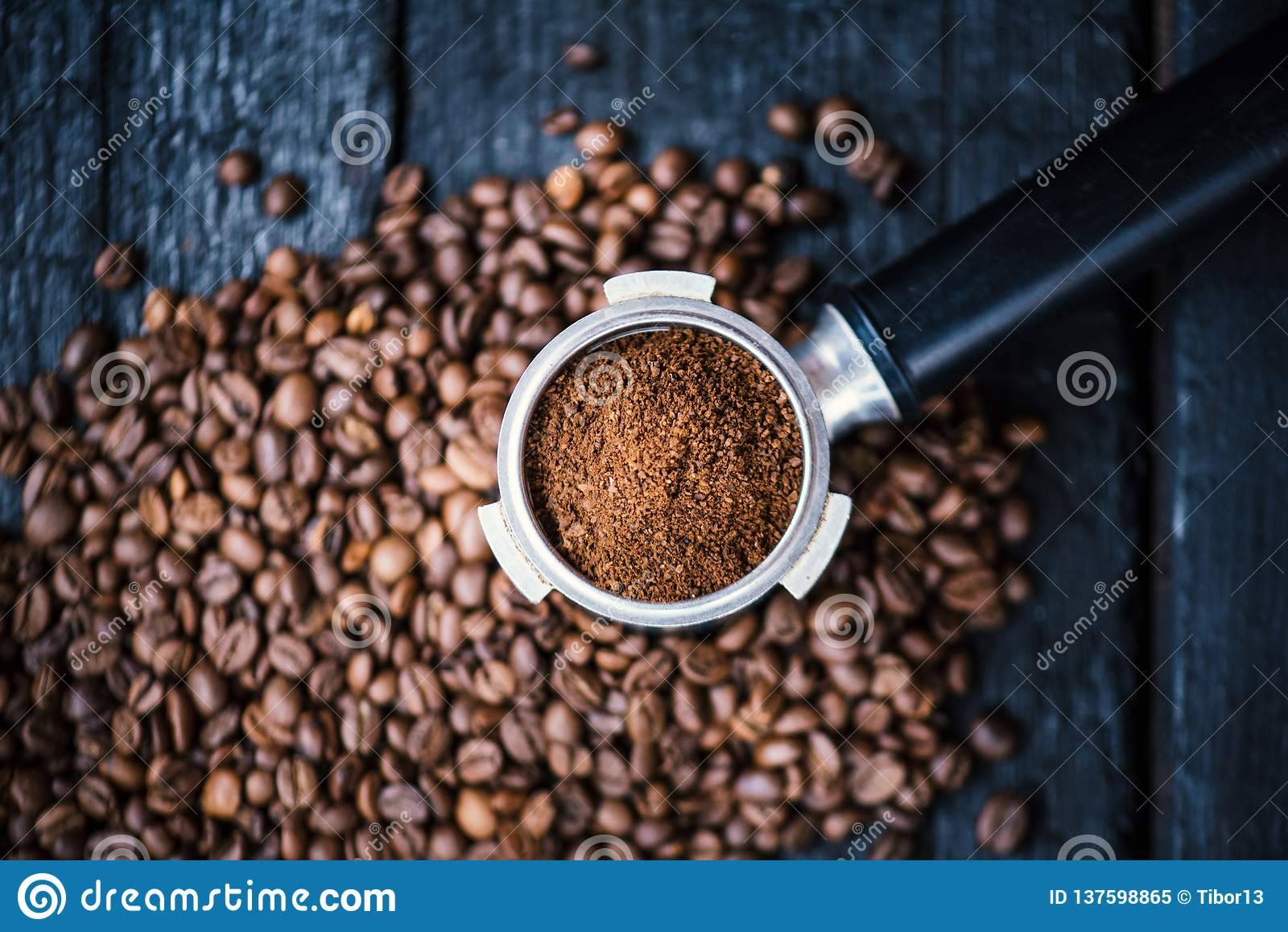 无底的过滤器用在一张木黑桌上的研磨豆 烤的豆咖啡 浓咖啡咖啡提取 准备浓咖啡