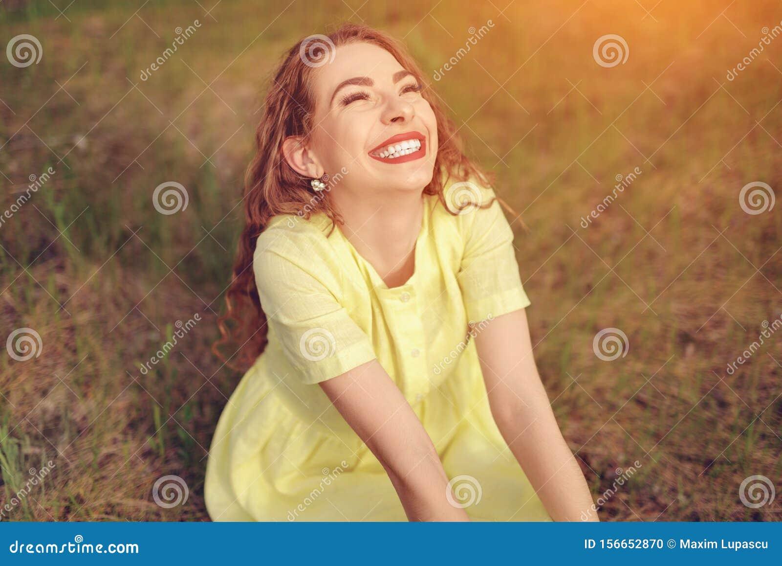 无忧无虑的妇女笑的坐在领域