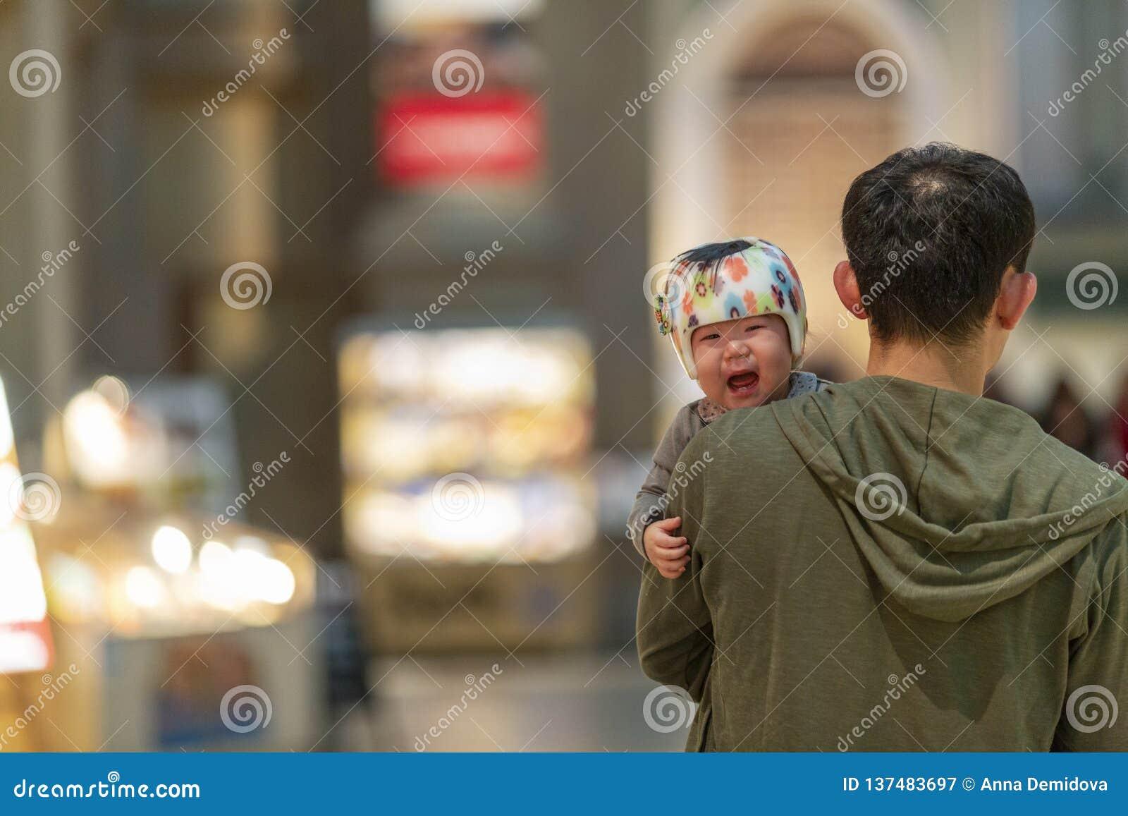 日本,东京,04/08/2017 爸爸的胳膊的一个哭泣的亚裔孩子
