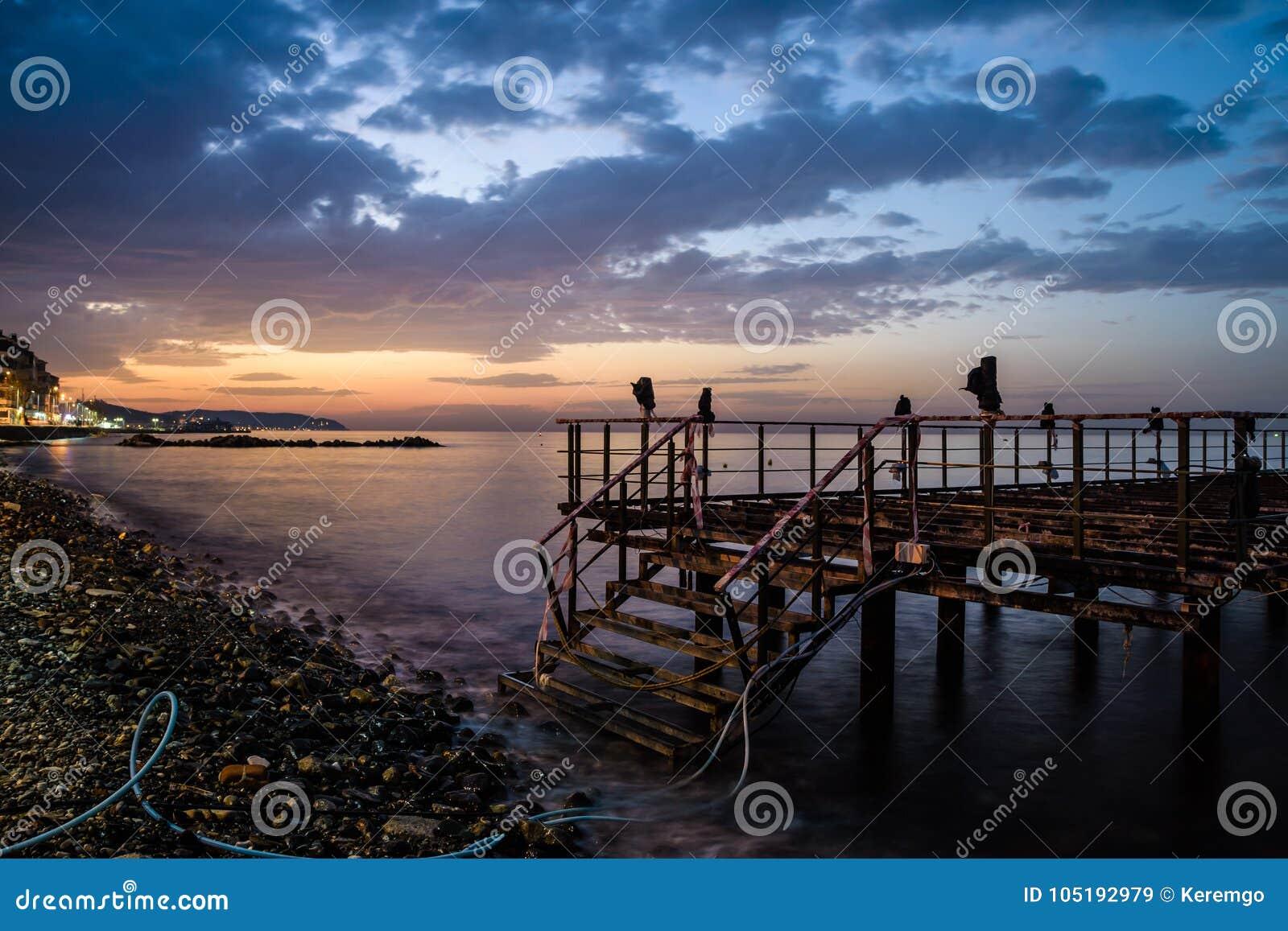 日落的使荒凉的船坞与风平浪静