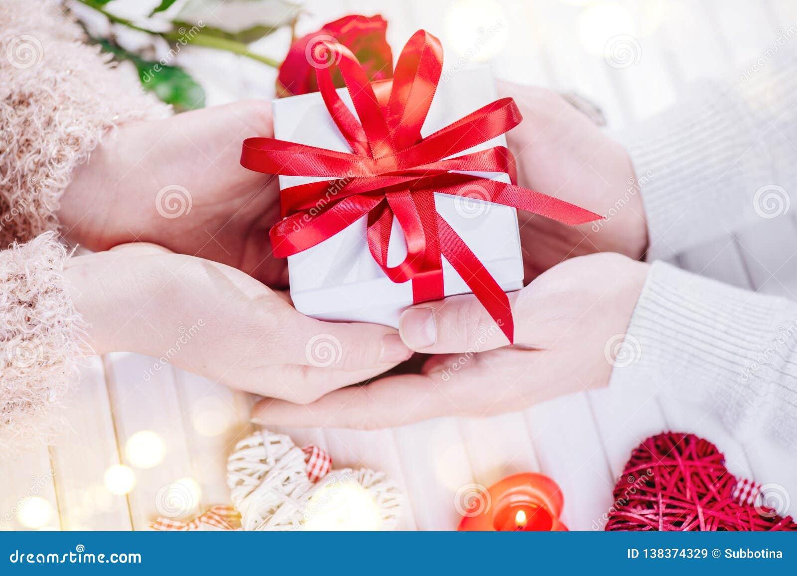 日s华伦泰 年轻夫妇递拿着在白色木背景的礼物盒 概念亲吻妇女的爱人