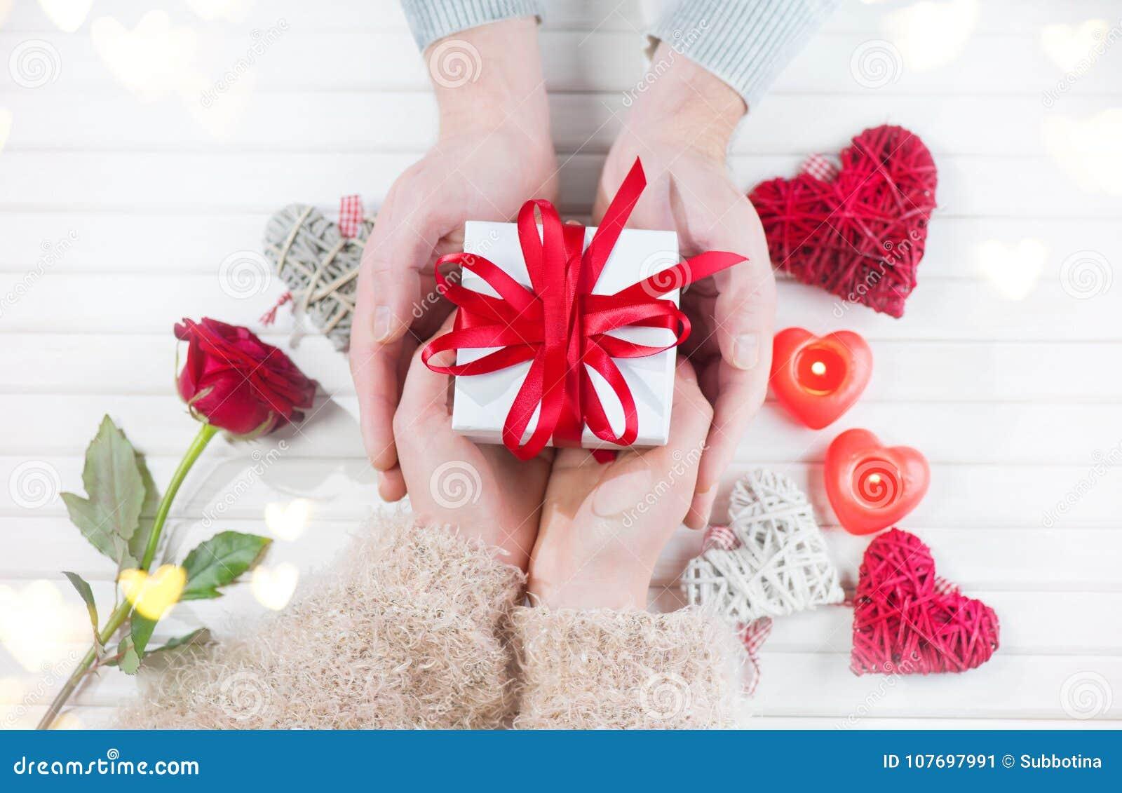 日s华伦泰 年轻夫妇递拿着在白色木背景的礼物盒
