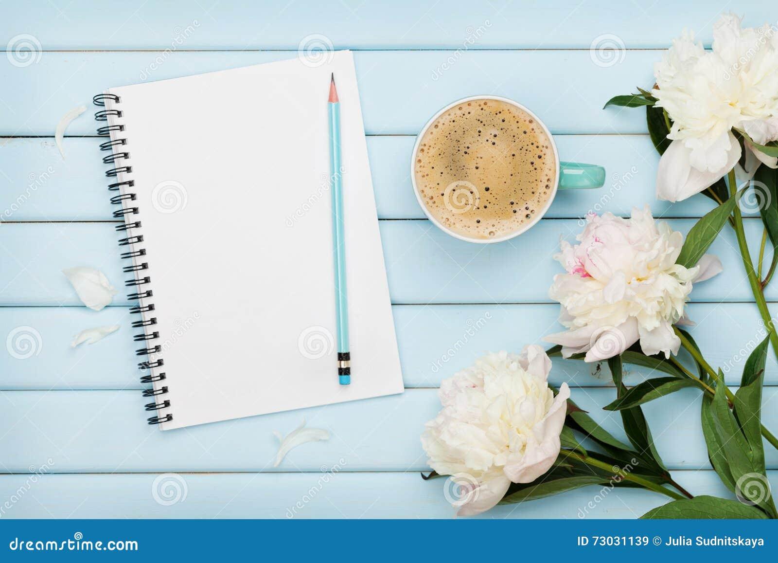早晨咖啡杯、空的笔记本、铅笔和白色牡丹在蓝色木桌,舒适夏天早餐,顶视图,平展位置上开花