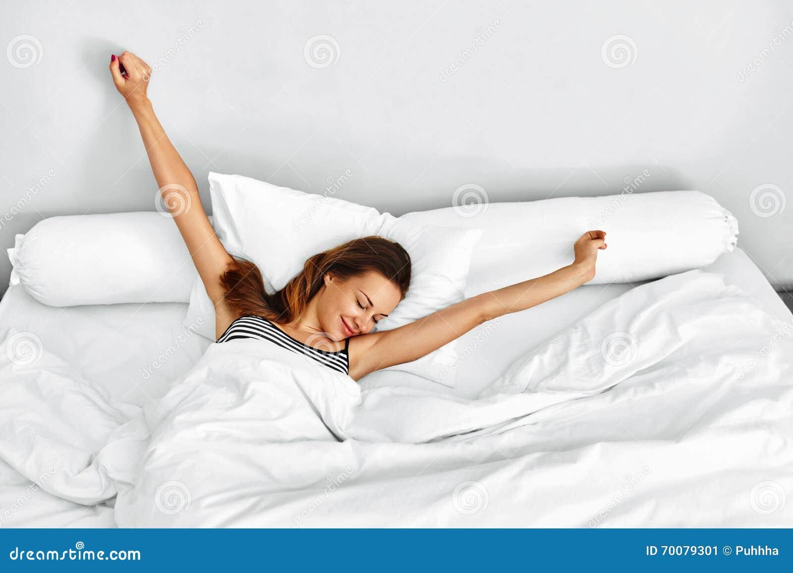 早晨醒 醒来舒展在床上的妇女 健康生活方式