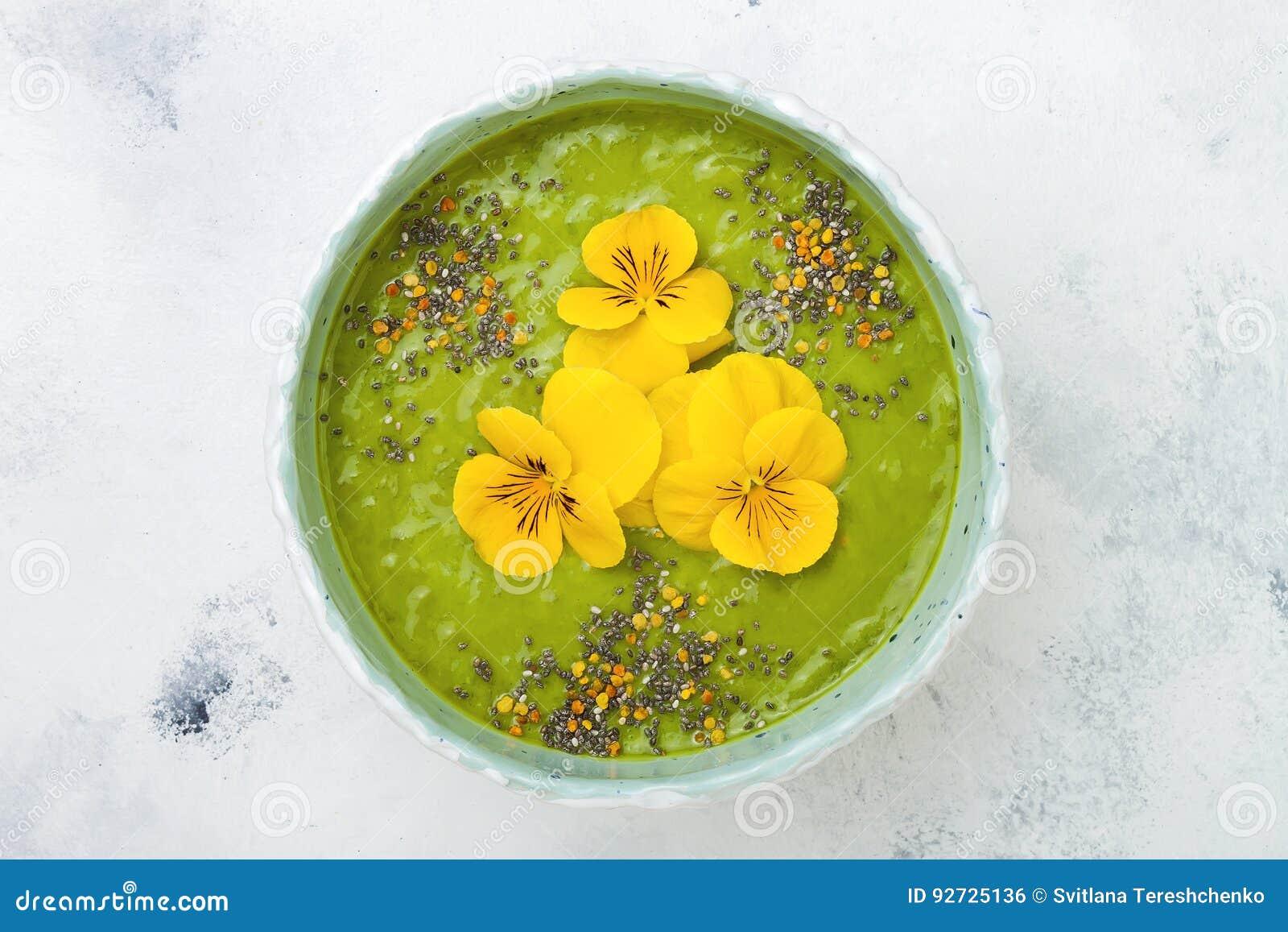 早餐戒毒所绿色圆滑的人碗冠上了与superfoods、chia种子、蜂花粉和可食的花 顶上,平的位置