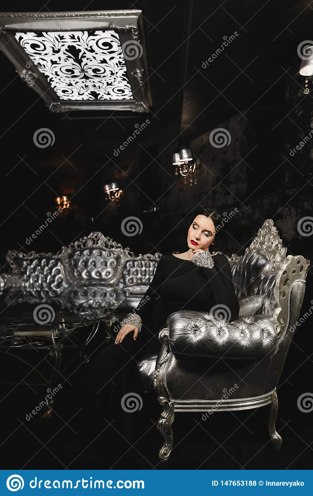时兴和性感的深色的式样妇女有完善的身体的和有在黑晚礼服的红色嘴唇的与坐