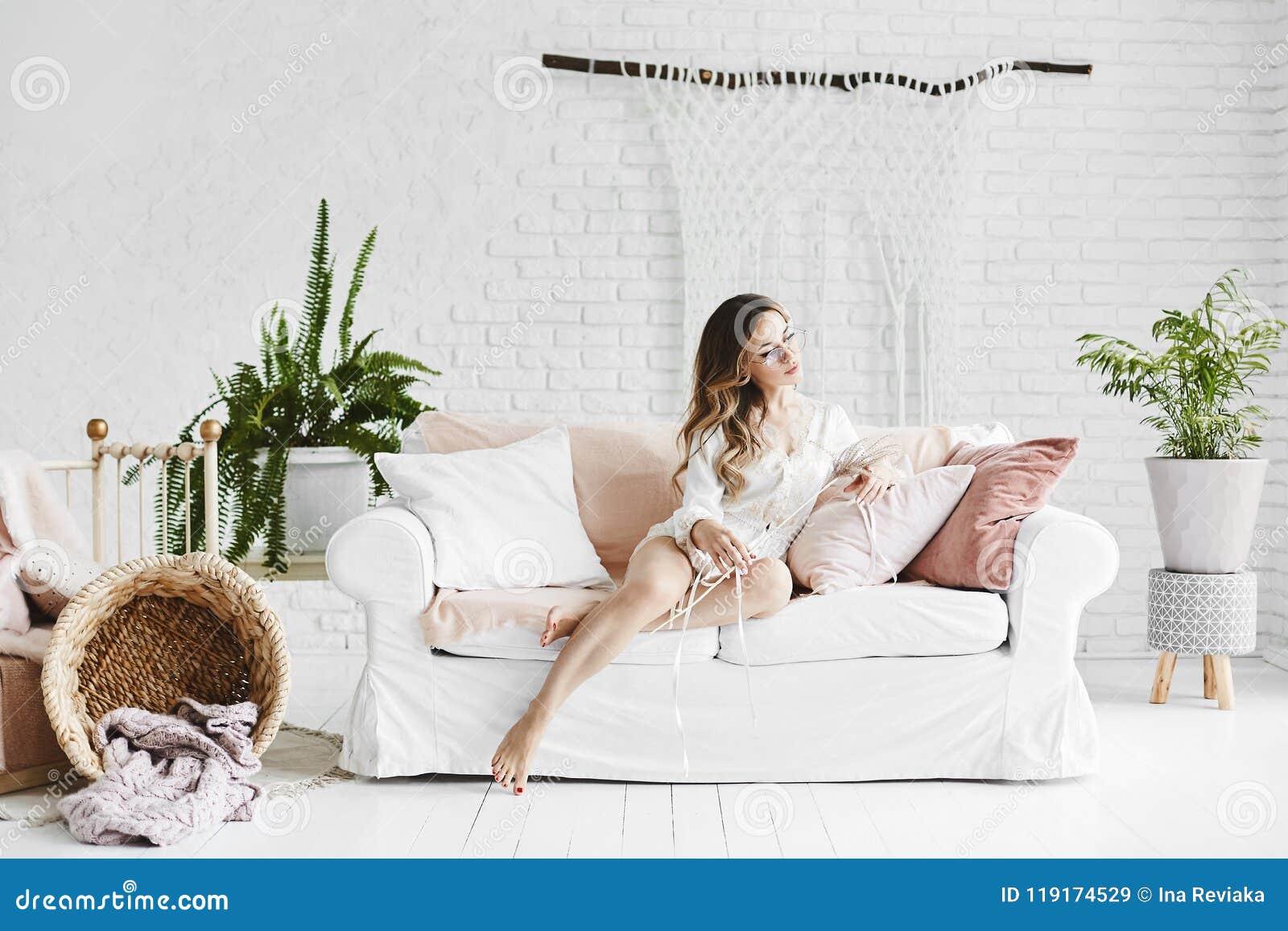时兴的玻璃和时髦的缎睡衣的肉欲和美丽的白肤金发的式样女孩,坐有枕头的白色沙发和