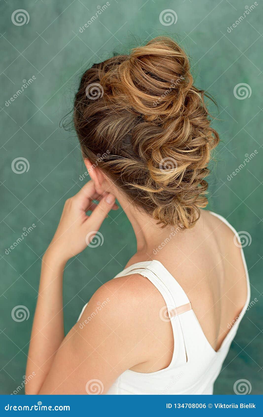 时尚一个美丽的深色的夫人的演播室画象有一种别致的发型的在一件白色女衬衫的eroquez样式