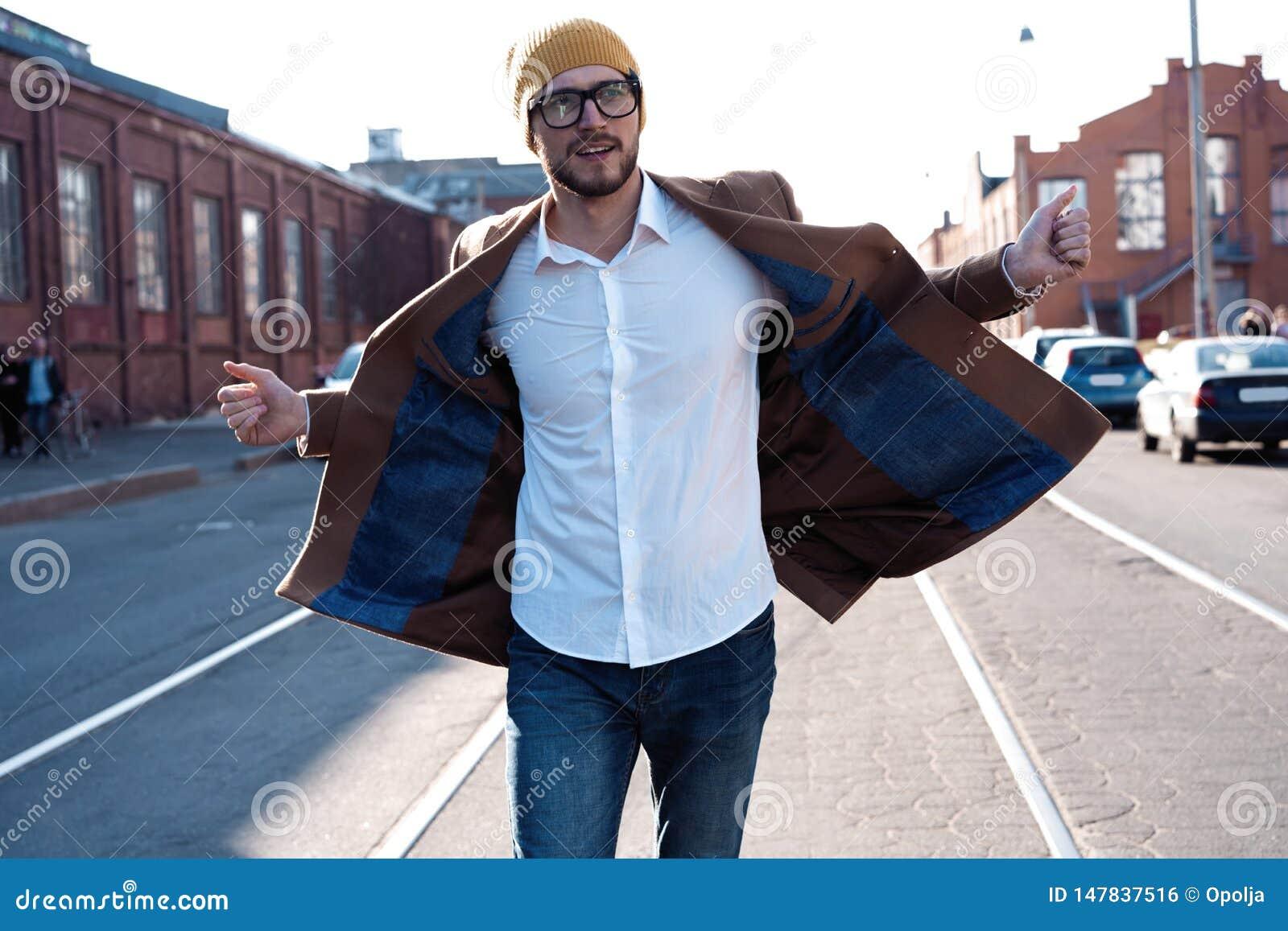 时尚人画象 玻璃的年轻人穿外套步行沿着向下街道的