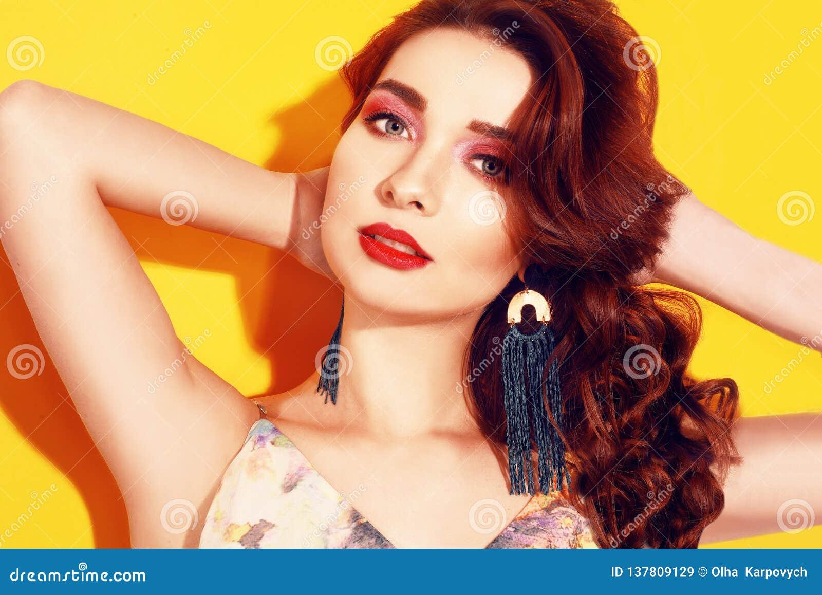 时尚在黄色背景摆在的女孩画象 有长期cerly头发的俏丽的深色的女孩和桃红色组成 有长期的女孩