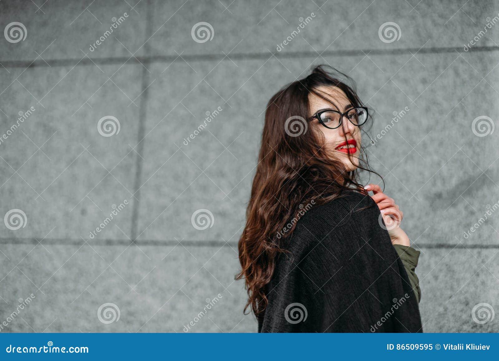 时尚概念:有长的头发、玻璃、红色嘴唇站立在现代墙壁附近的佩带在绿色衣服和灰色je的美丽的女孩