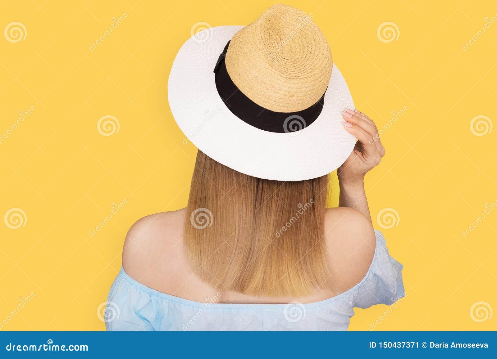 时尚神色,相当凉快的年轻女人式样身分,戴一个典雅的帽子和在黄色背景的蓝色礼服