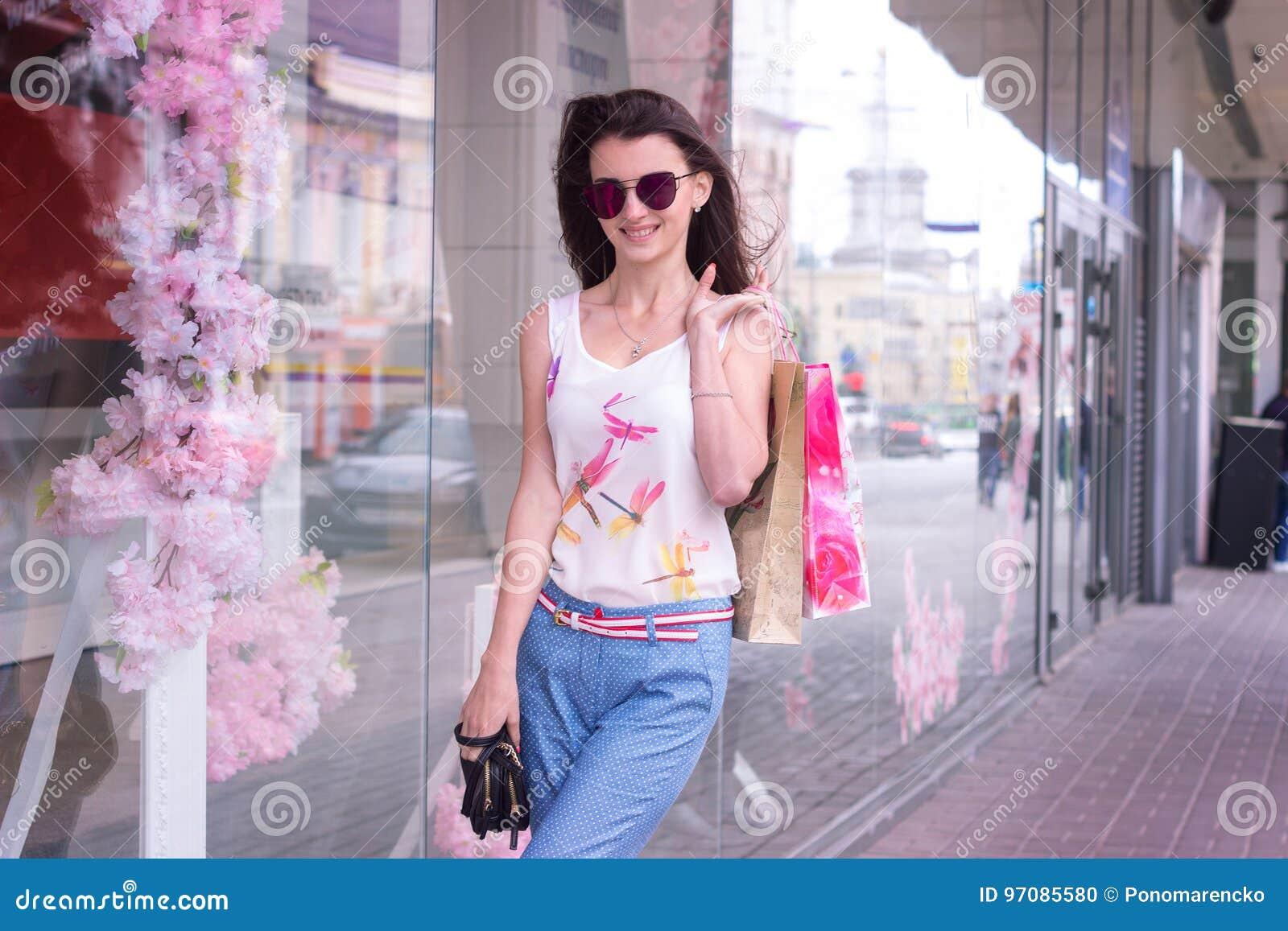 时尚美丽的妇女在玻璃和包裹的城市四处走动