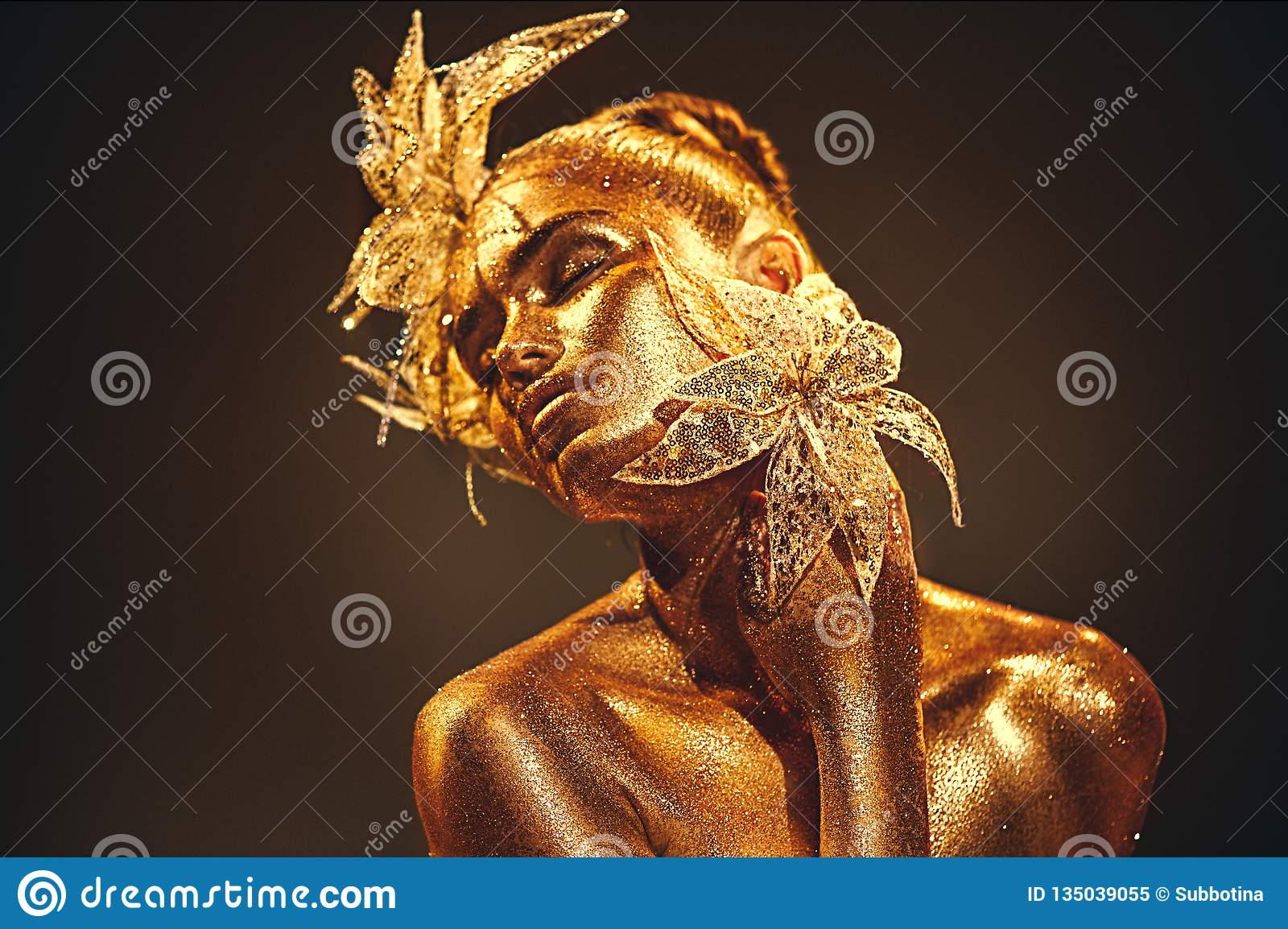 时尚金有明亮的金黄闪闪发光的模型妇女在摆在的皮肤,幻想花 美女画象有发光的makeu的