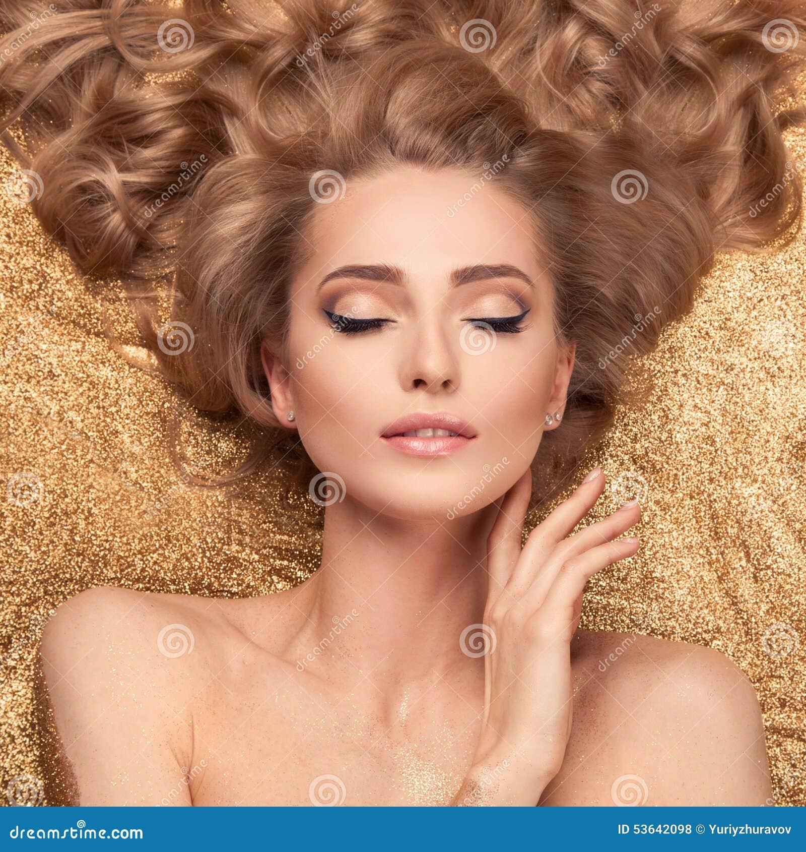 时尚说谎在金黄闪烁的秀丽女孩