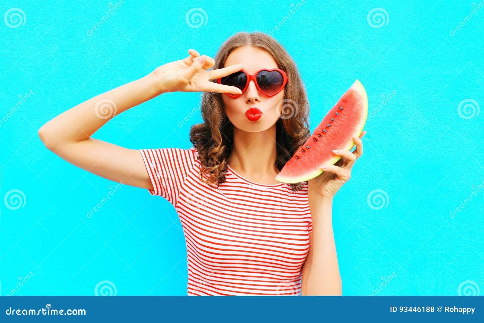 时尚画象妇女拿着切片西瓜和吹的嘴唇