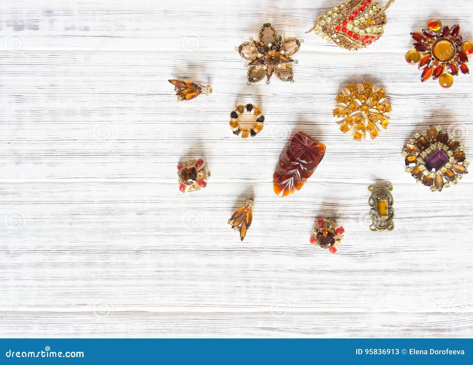 时装模特儿首饰 葡萄酒首饰背景 美丽的明亮的假钻石别针和耳环在白色木头 平的位置,顶视图