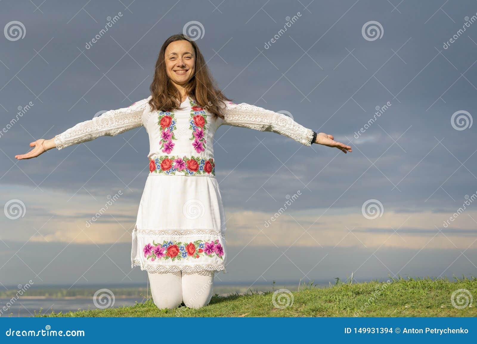 时装的美女在剧烈的天空的背景 全国衣裳的性感的妇女 r