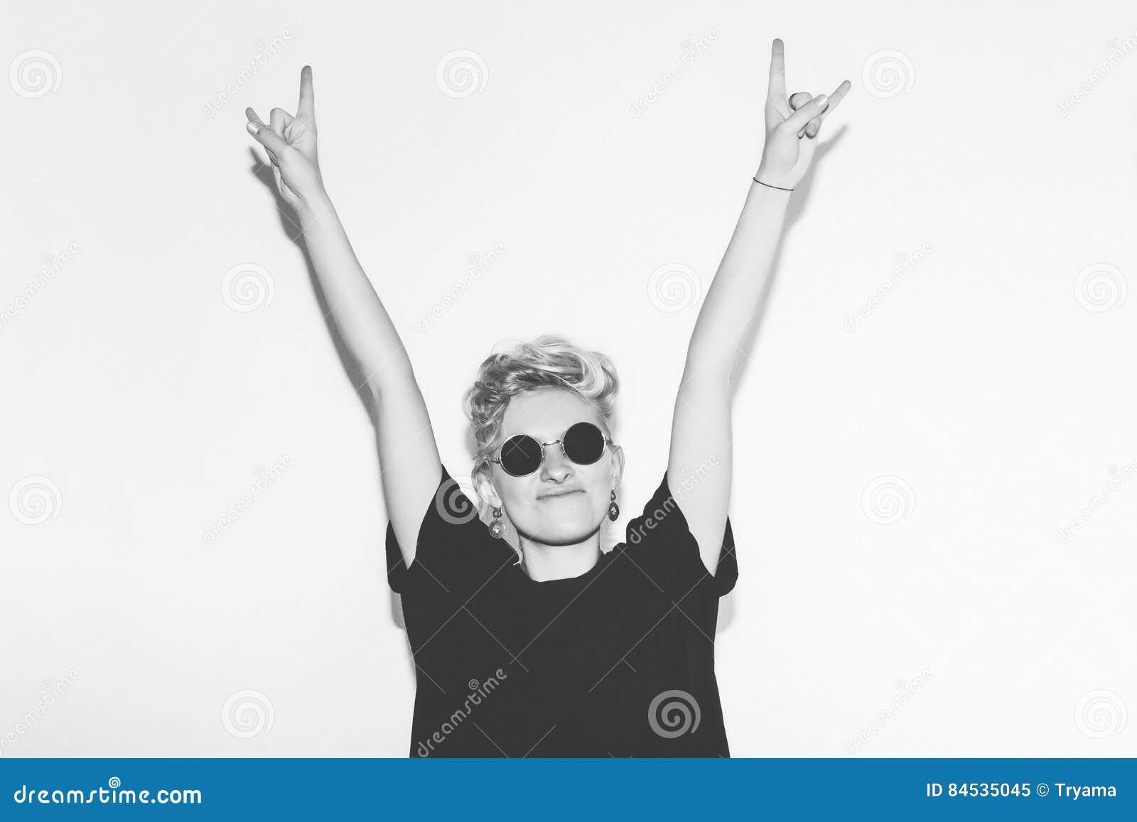 时髦的一件黑T恤杉和岩石太阳镜的时尚性感的白肤金发的坏女孩 危险岩石情感妇女给