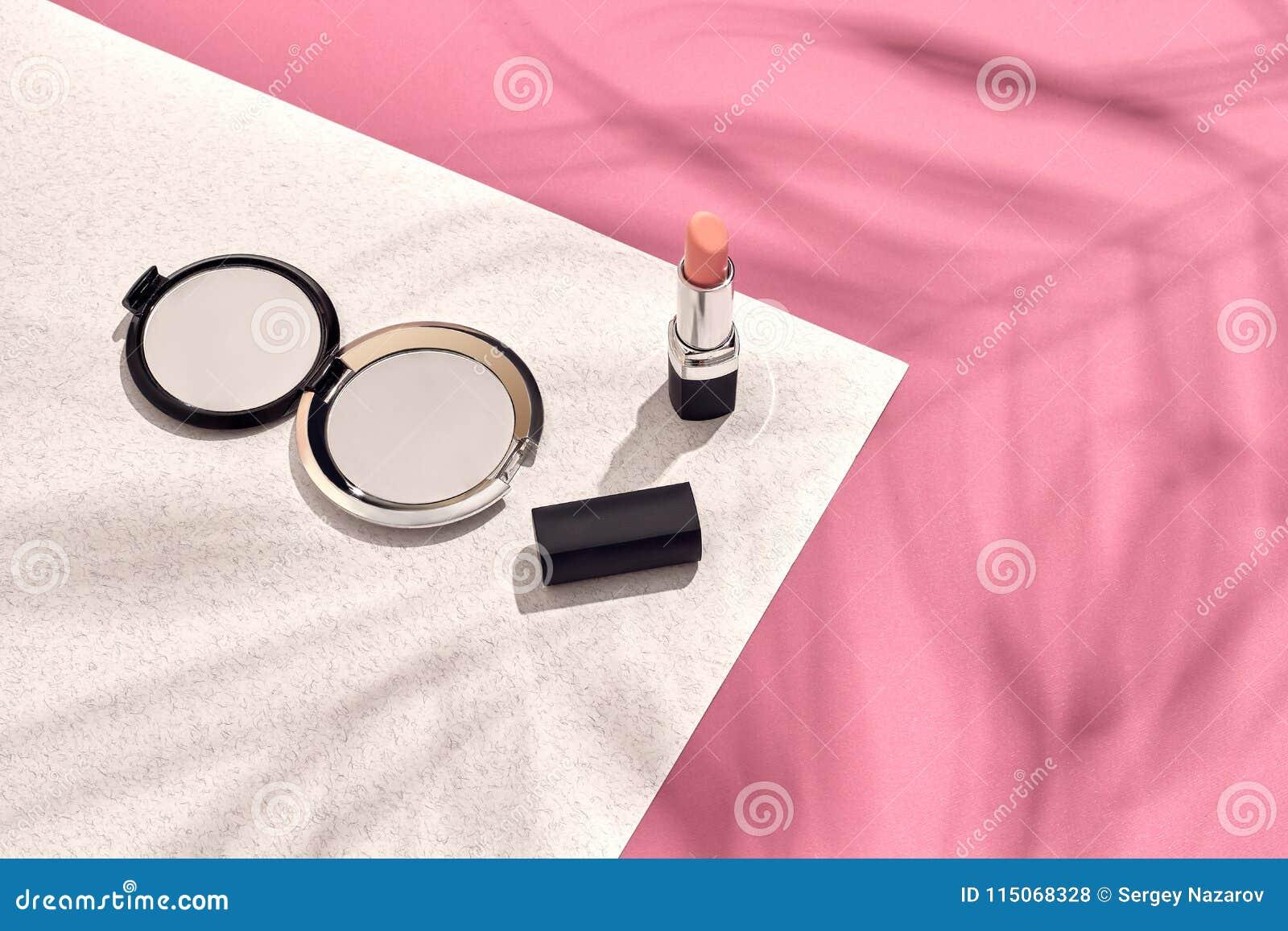 时髦的女人` s化妆用品和辅助部件 平的位置 背景桃红色白色 从棕榈叶的阴影