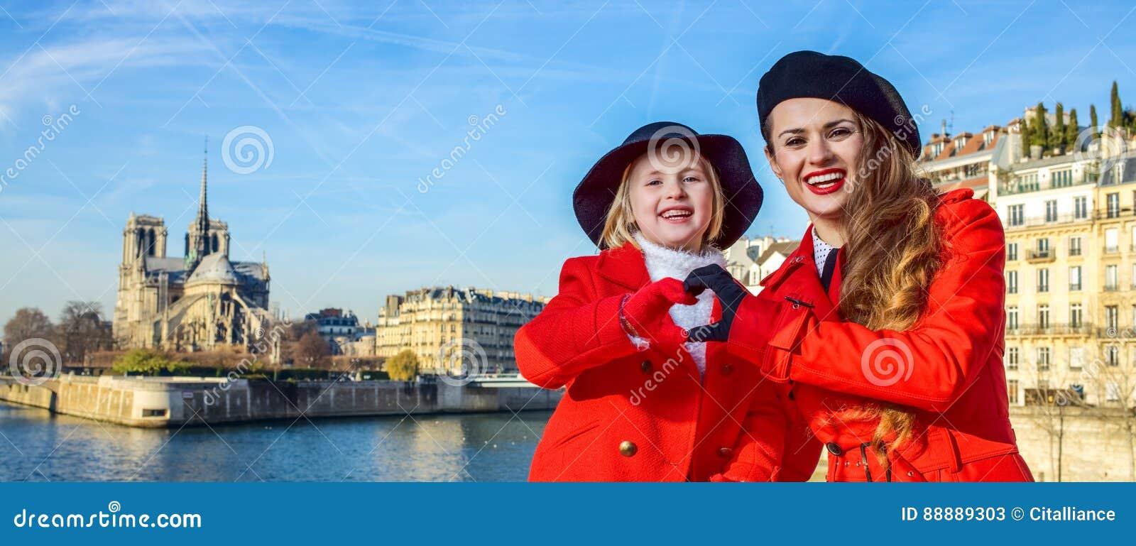 时髦的母亲和女儿在显示心形的手的巴黎