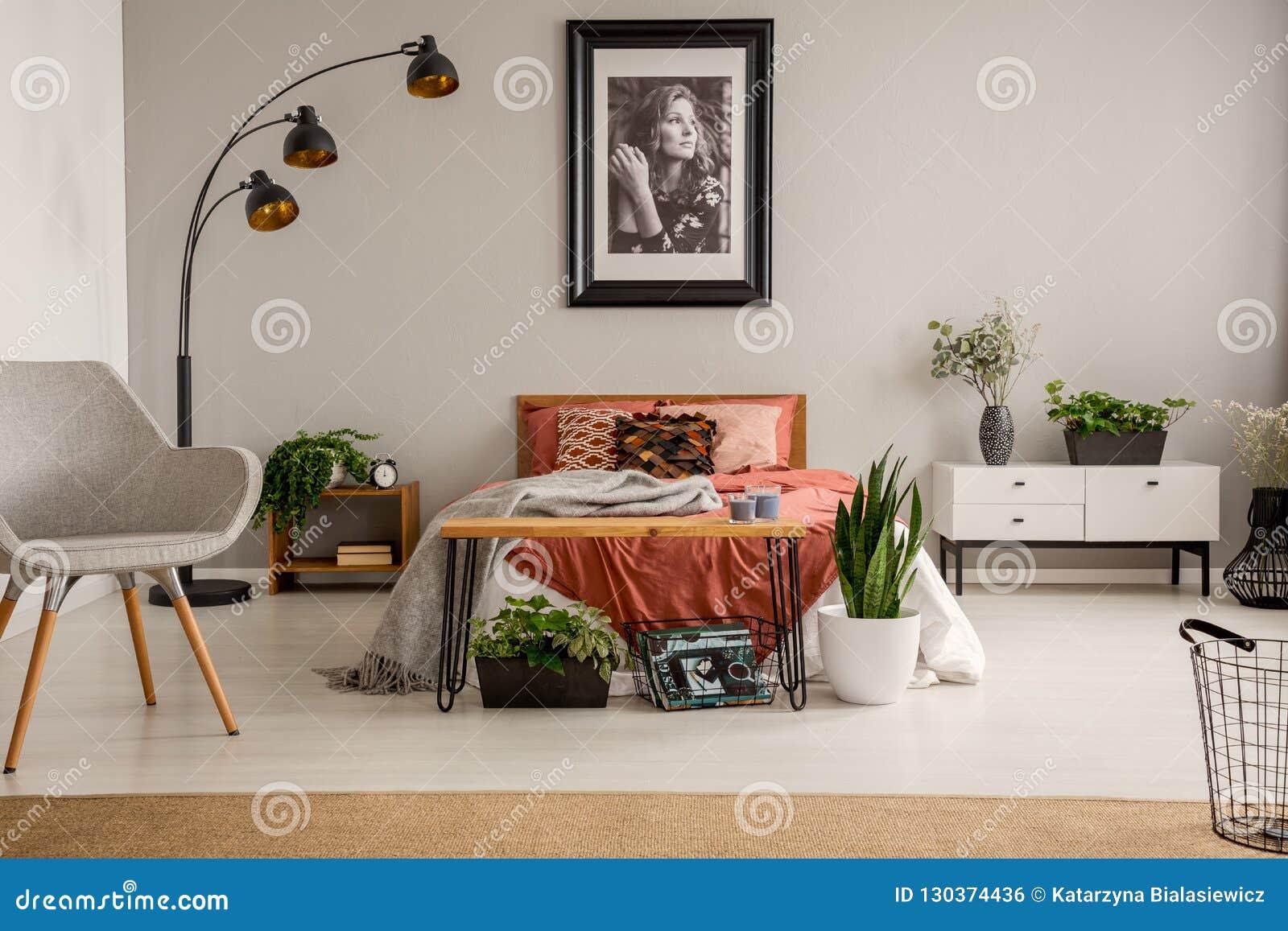 时髦的灰色椅子、黑灯、海报在墙壁上和加长型的床与铁锈颜色卧具在时髦的舱内甲板明亮的卧室