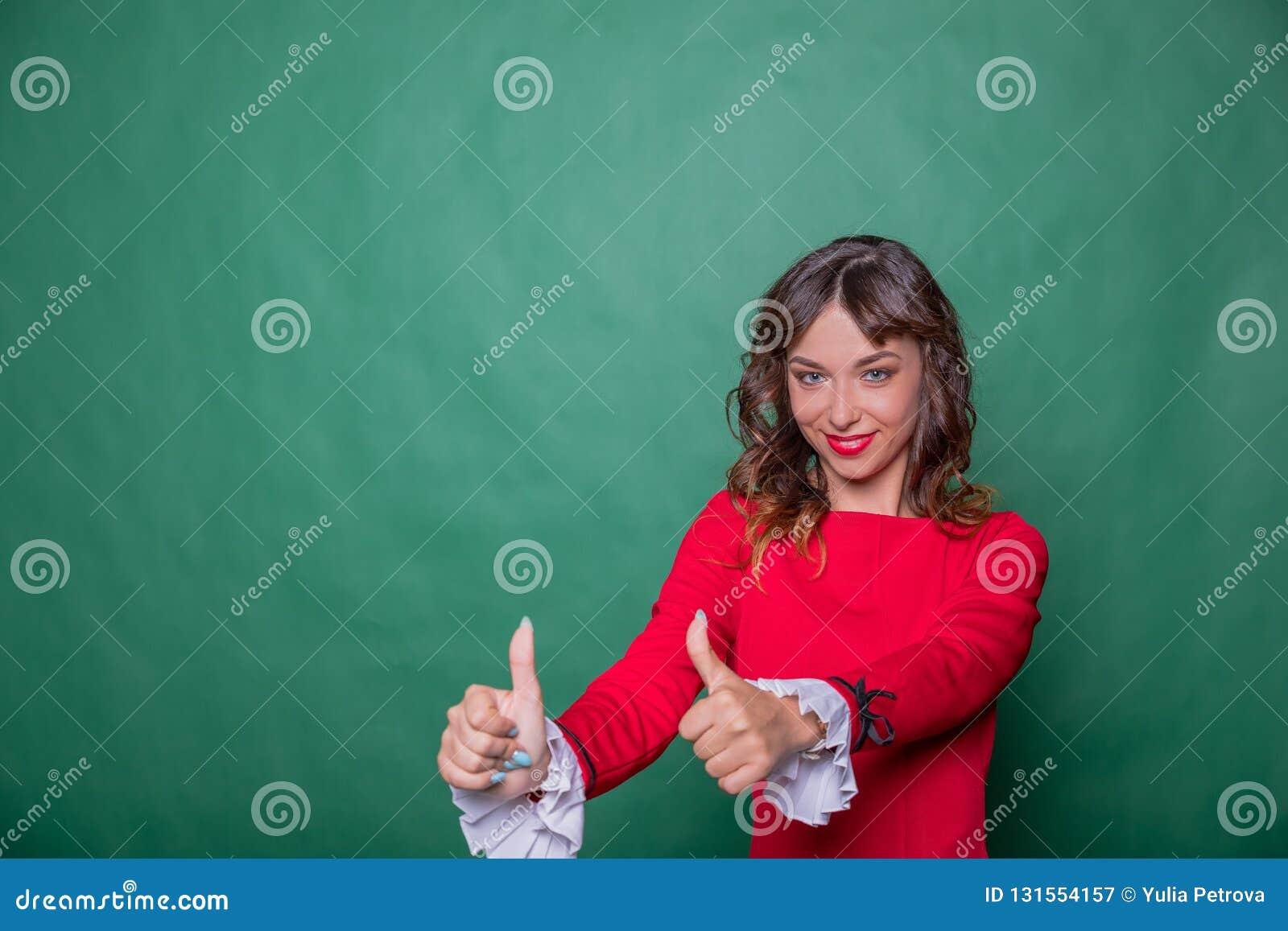 时髦的红色礼服陈列赞许标志的愉快的成功的美女由两只手 查出在绿色背景