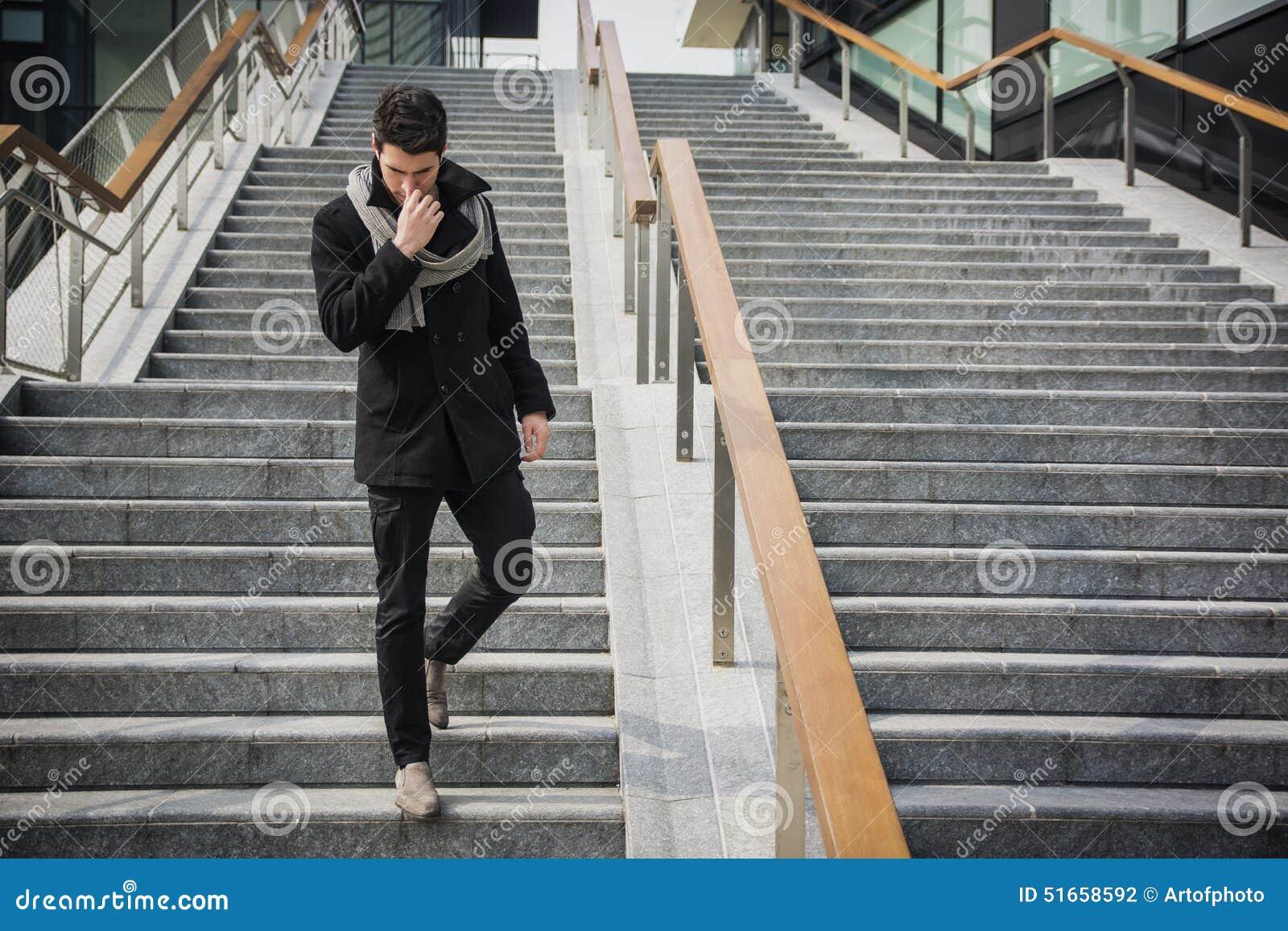 时髦英俊的年轻人以站立在一个长的楼梯的冬天时尚
