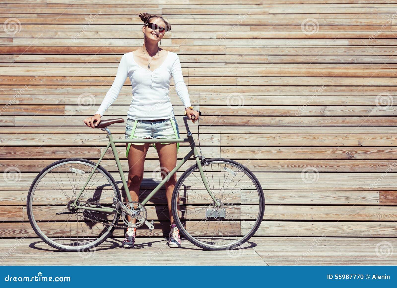 时兴的美丽的年轻俏丽的女孩简而言之和与自行车的T恤杉立场固定在齿轮nex明亮木的板条墙壁