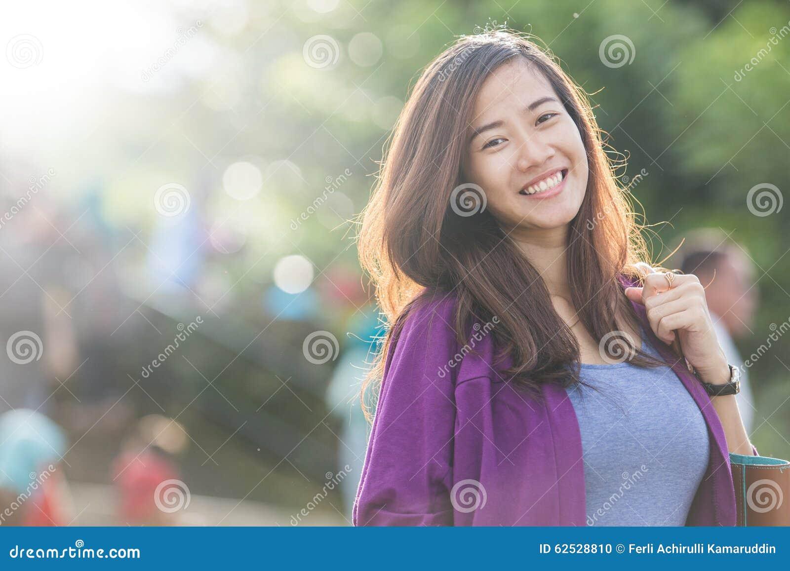 明亮地微笑对照相机的美丽的亚裔妇女