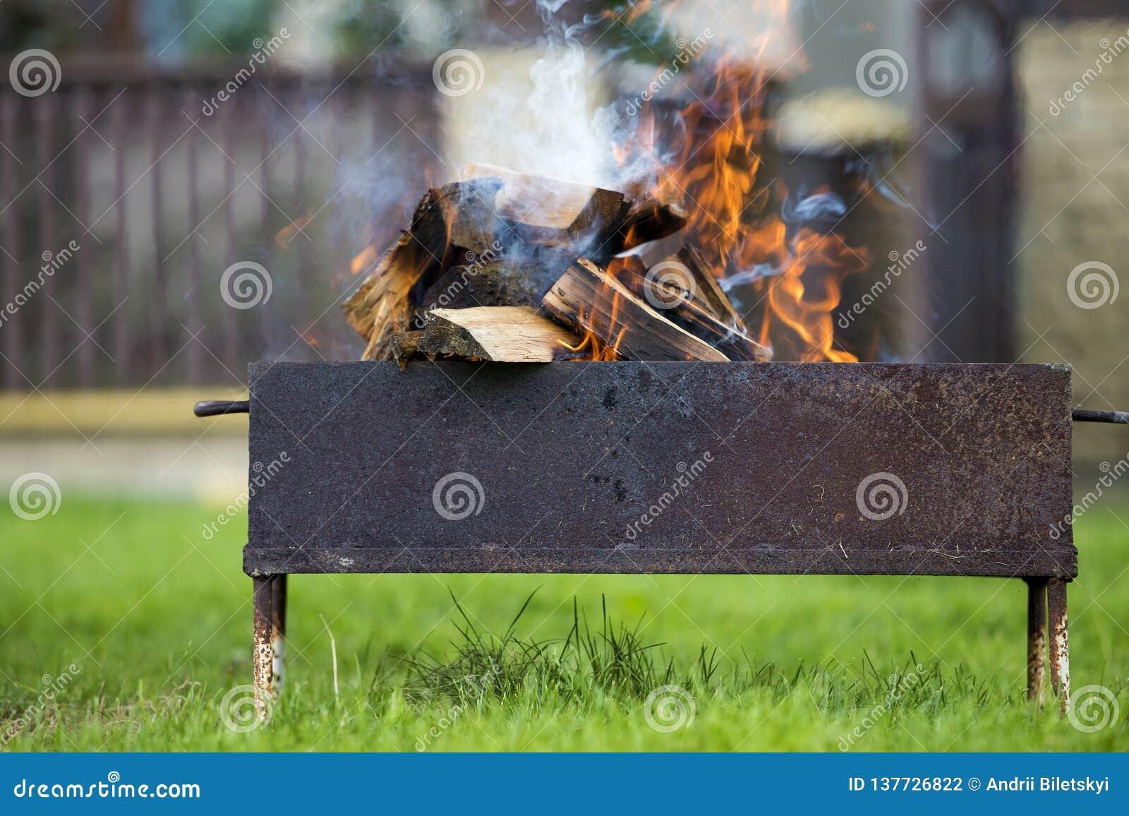 明亮地烧在金属烤肉的箱子木柴室外 野营,安全和旅游业概念