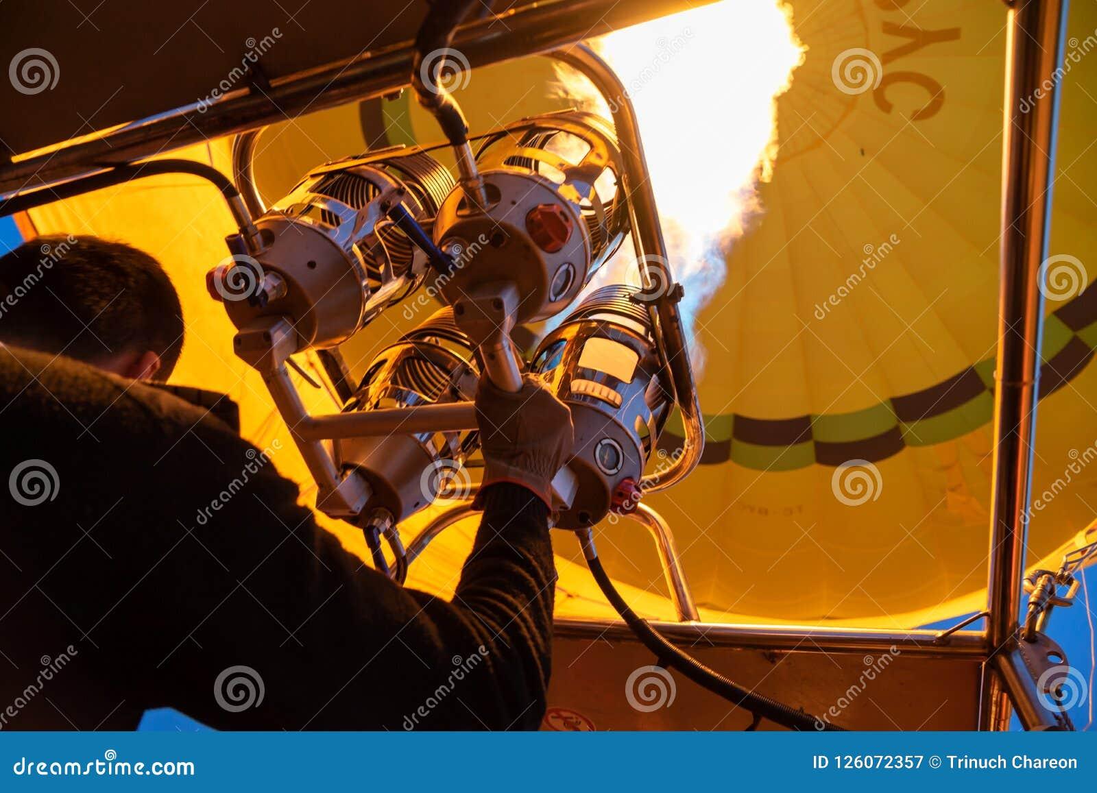明亮的黄色热空气气球飞行用煤气取暖器火焰由飞行员的热设备在卡帕多细亚,从里边低角度视图