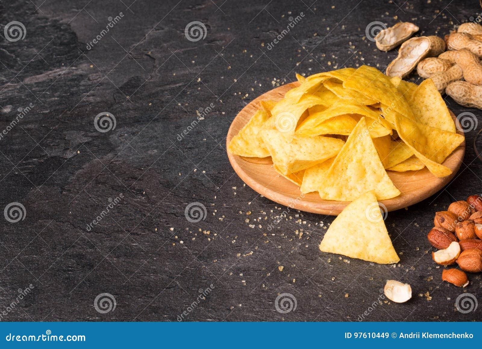 明亮的黄色烤干酪辣味玉米片顶视图在一块轻的木圆的板材的 与混杂的坚果的玉米片在黑背景