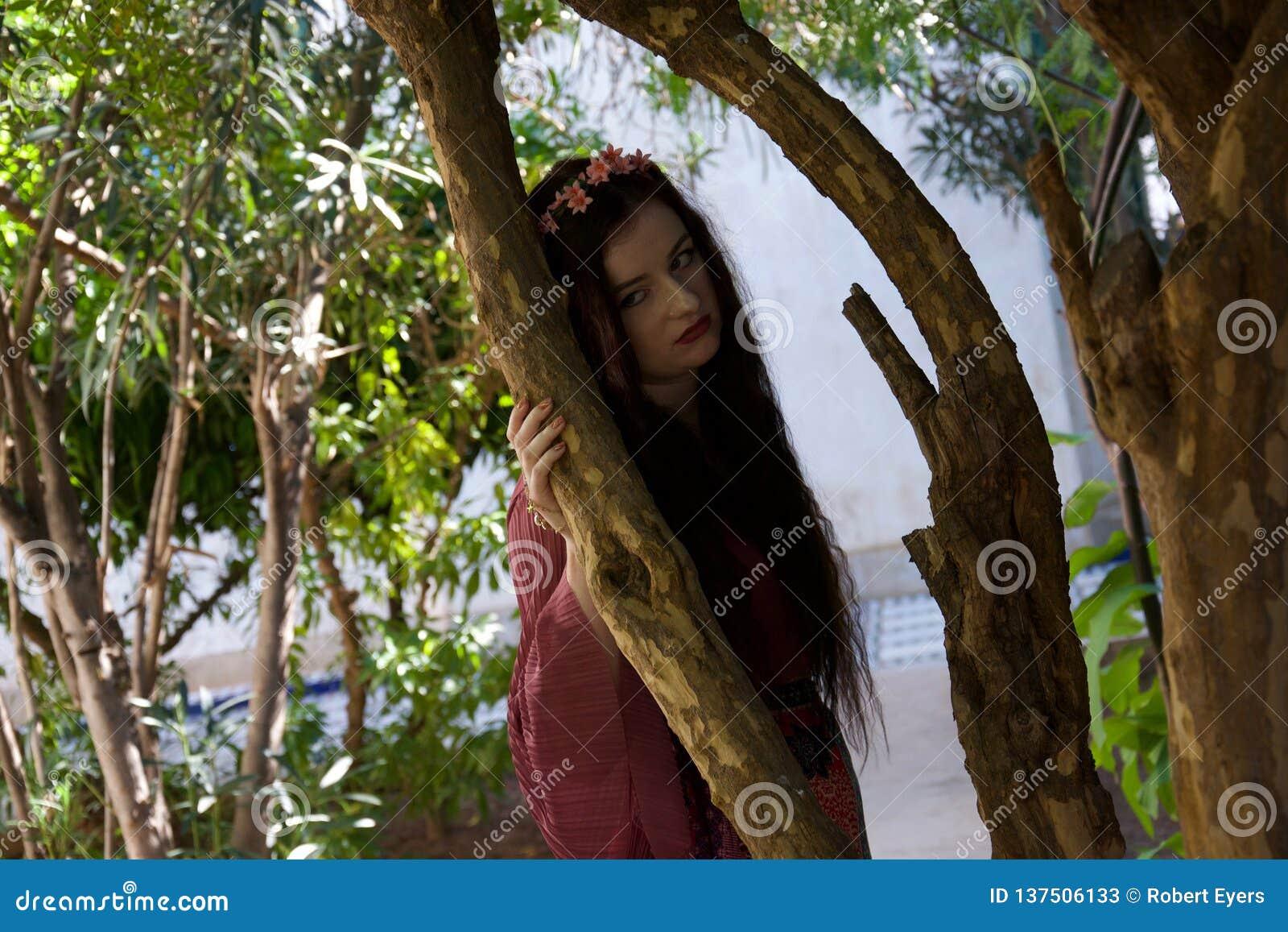易怒的嬉皮女孩倾斜反对树