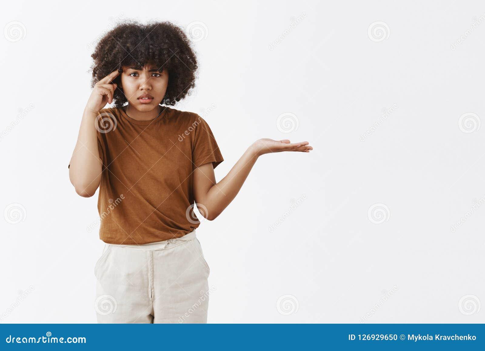 是您沉默寡言或愚笨 懊恼和小便的被问的非裔美国人的妇女画象有非洲发型耸肩的