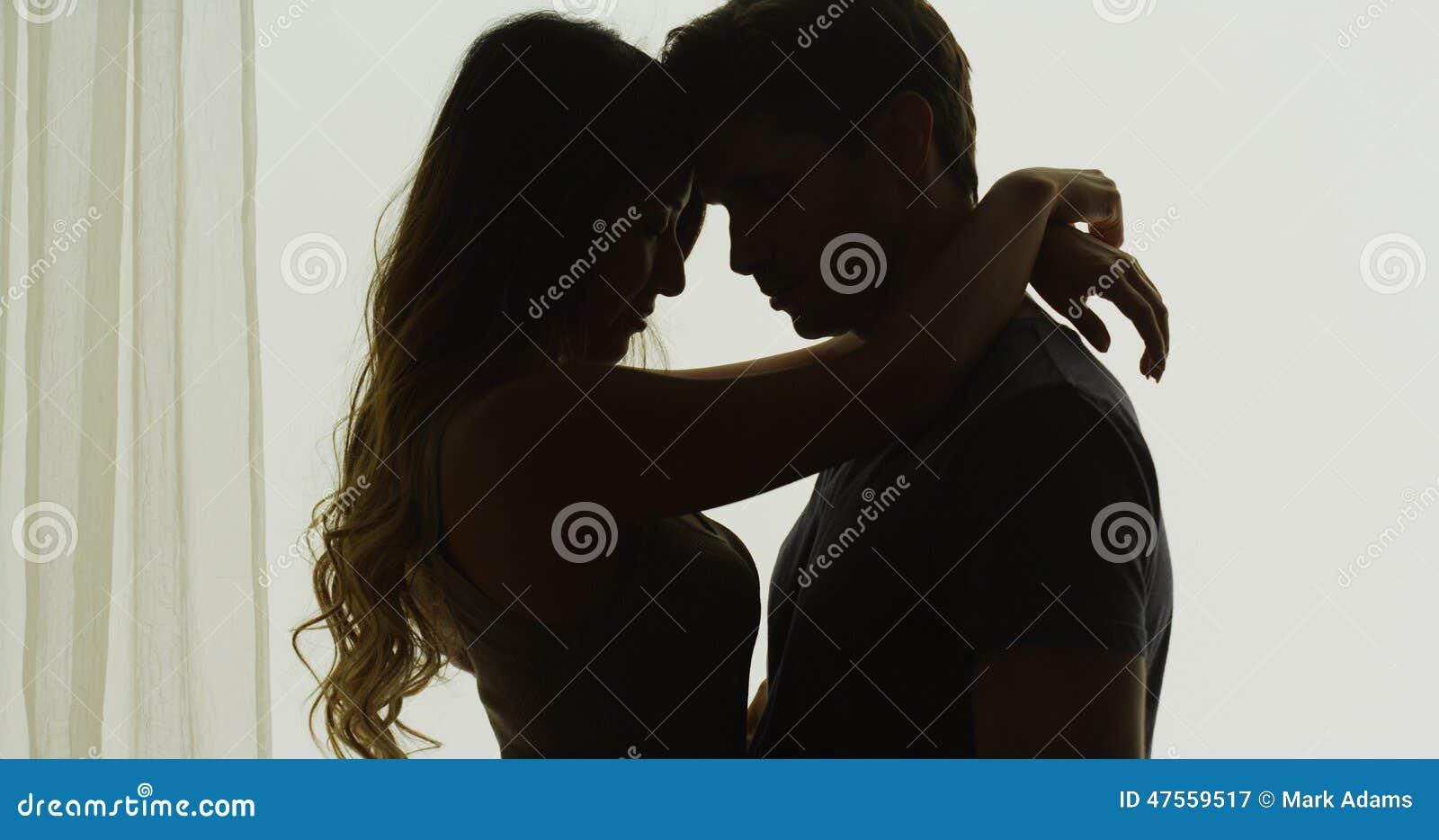 是的夫妇剪影亲密的在窗口前面