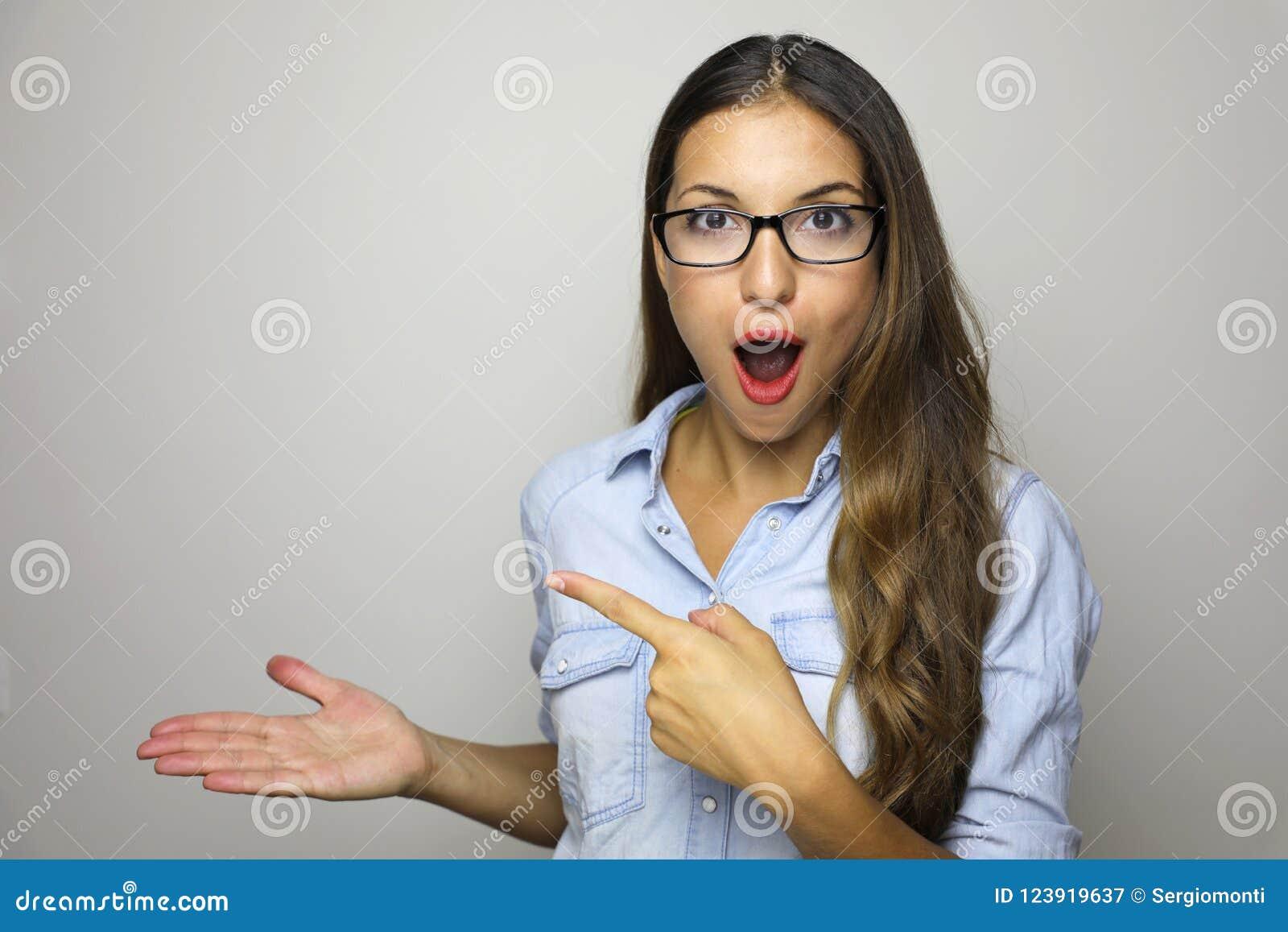 显示与开放手棕榈的产品和指向手指的少妇 在被隔绝的女实业家佩带的玻璃的激动的表示