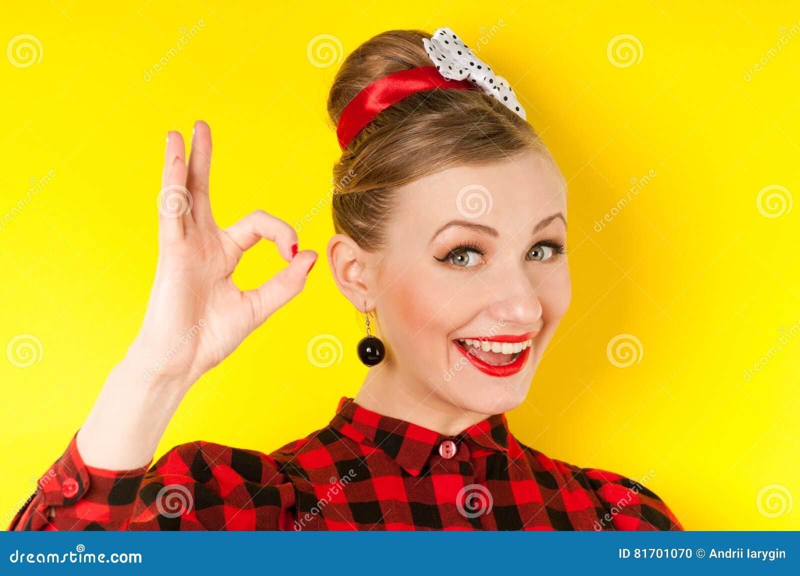 显示与手指的愉快的少妇好标志在一黄色backg