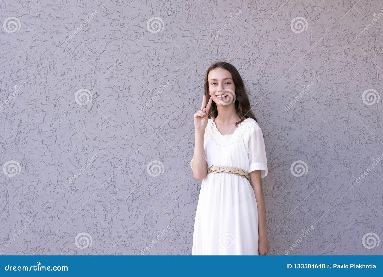 显示和平标志的俏丽的礼服的夫人