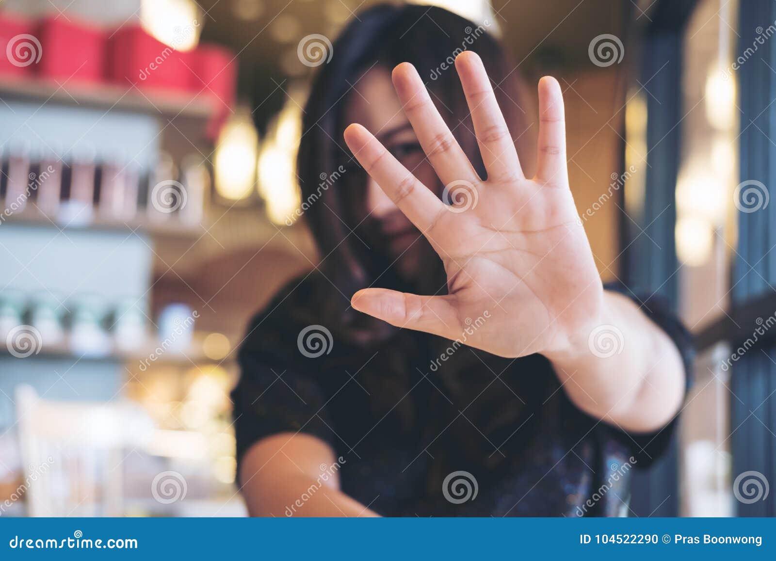 显示她的手标志的一名亚裔妇女盖她的面孔对某人说没有感到的恼怒