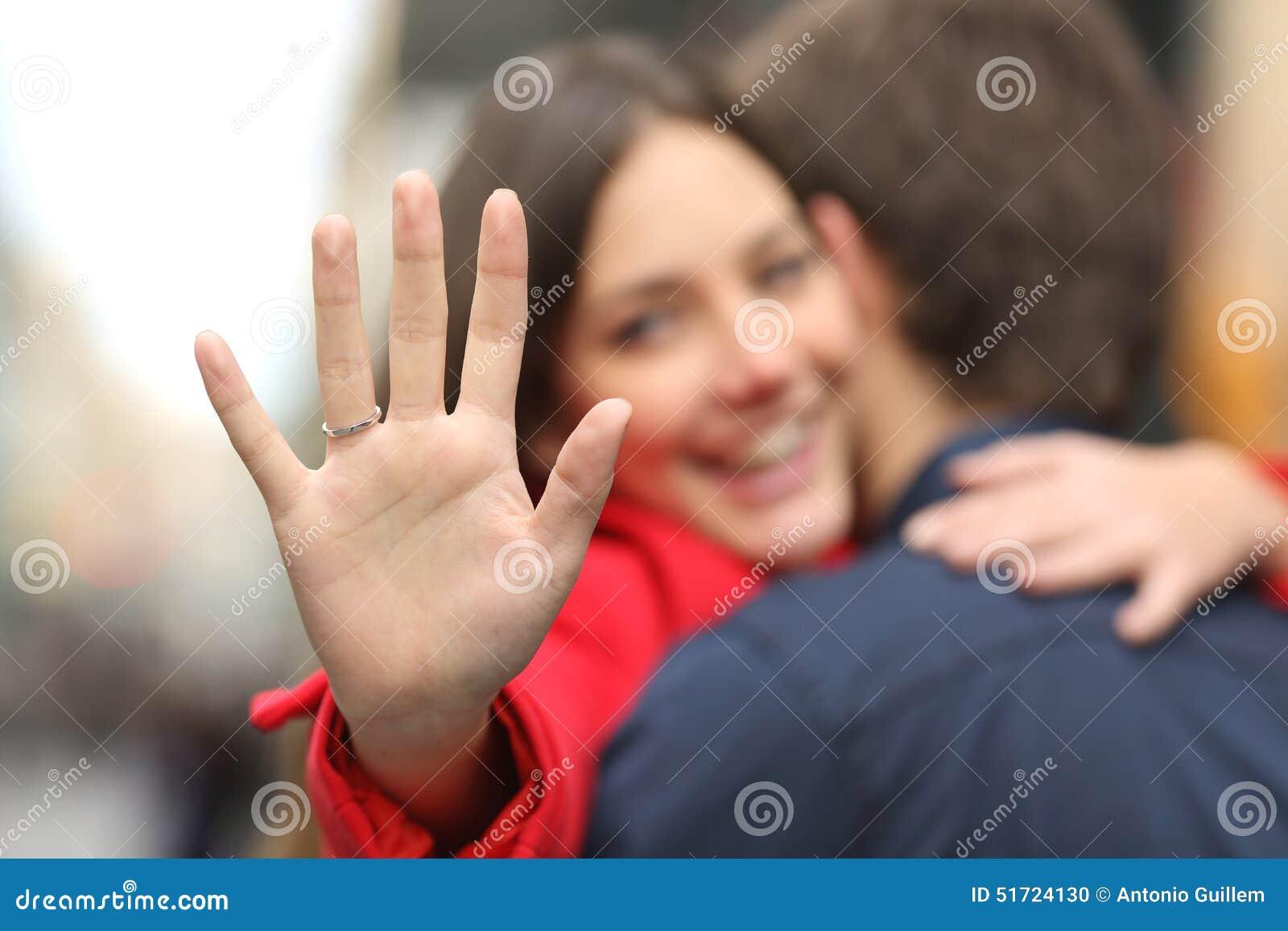 显示定婚戒指的愉快的妇女在提案以后