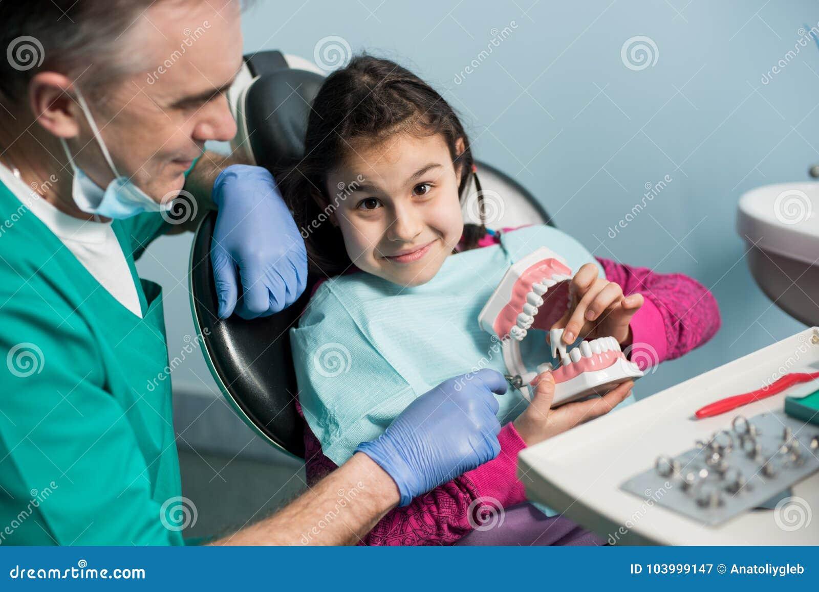 显示对女孩的小儿科牙医在牙医椅子牙齿下颌模型在牙齿办公室