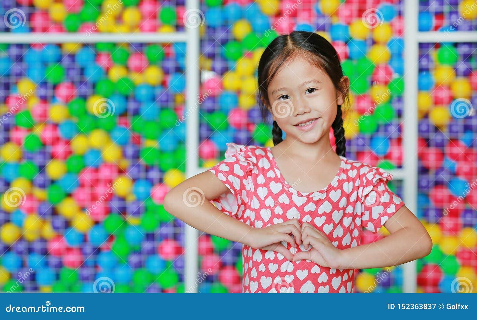 显示心脏标志的微笑的亚裔女孩画象反对五颜六色的球操场 表现出爱情感